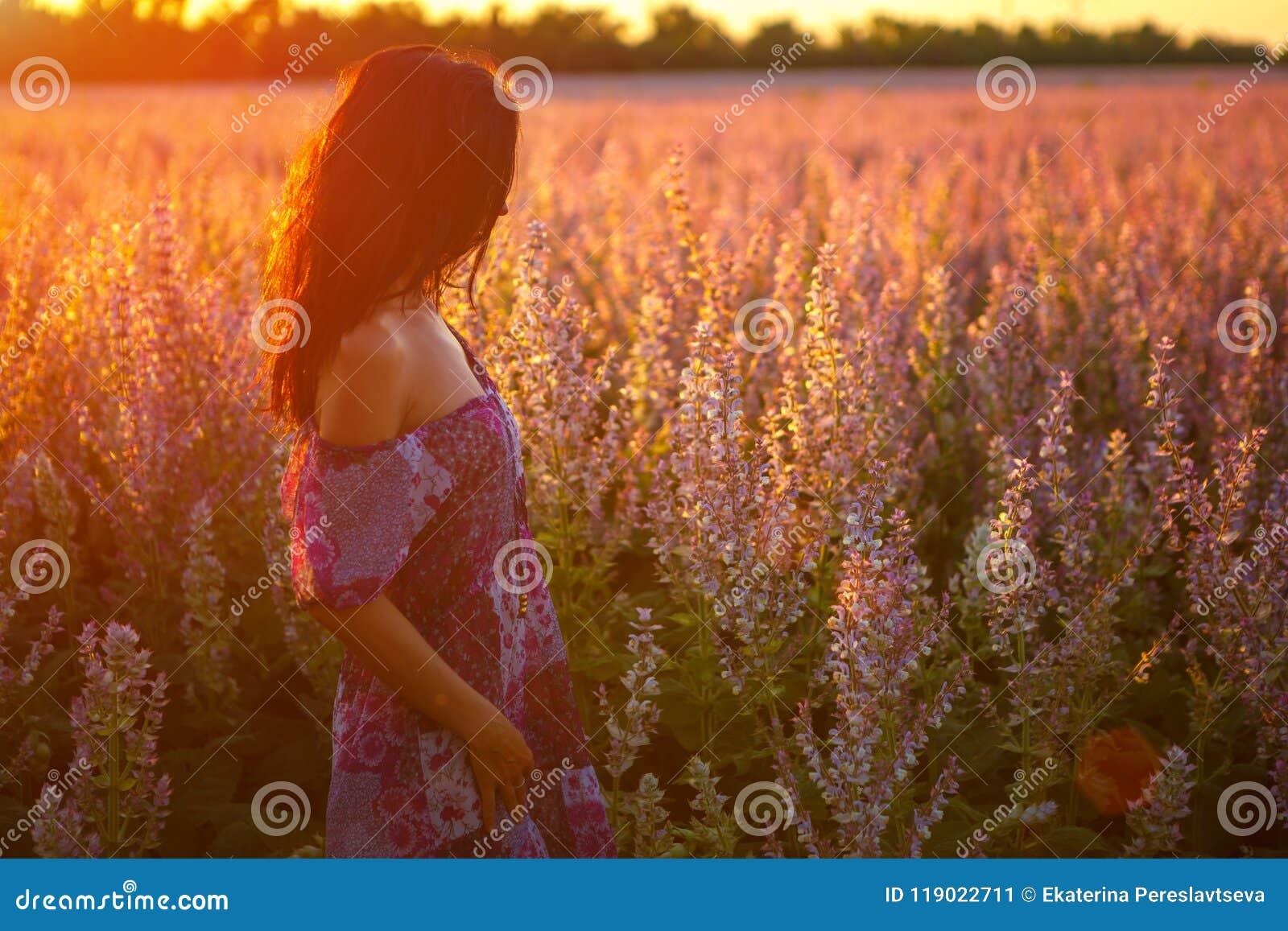 Portret dziewczyna w kwitnącym polu w słońcu przy zmierzchem pojęcie relaks
