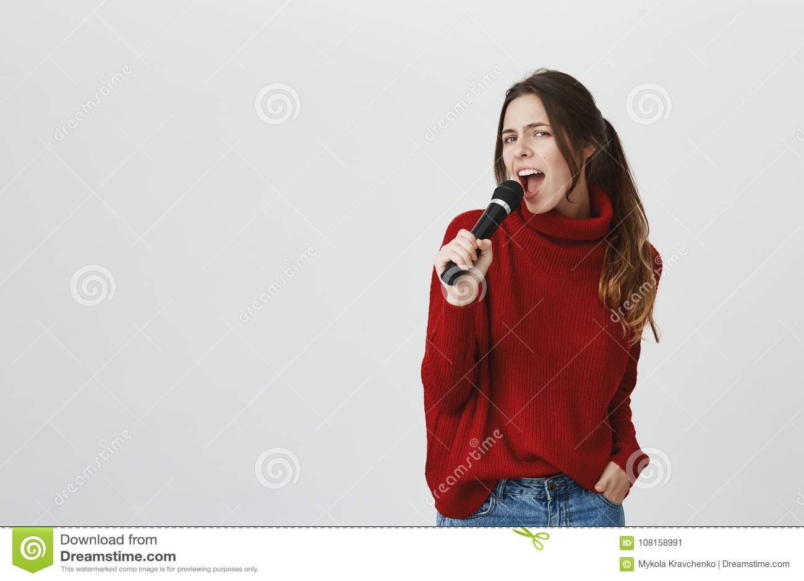 Portret elegancki piękny dziewczyna śpiew w karaoke, mienie mikrofon, jest ubranym ślicznego czerwonego zima pulower nad bielem