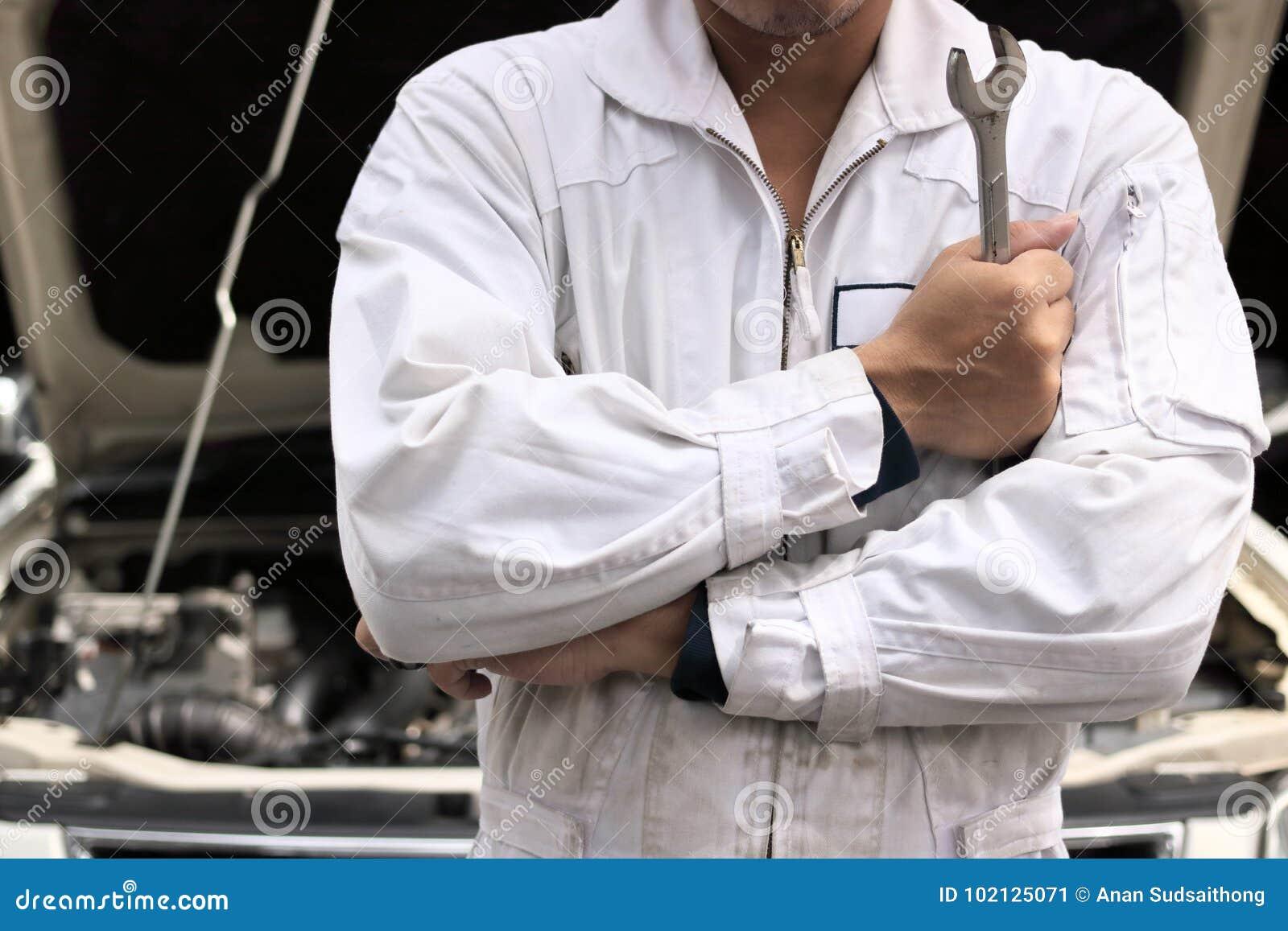 Portret fachowy młody mechanika mężczyzna w jednolitym mienia wyrwaniu przeciw samochodowi w otwartym kapiszonie przy remontowym