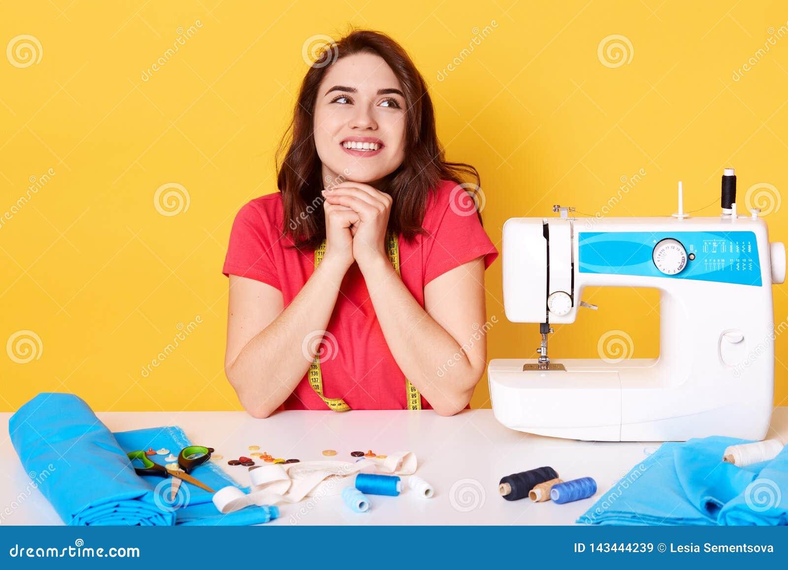 Portret fachowy pozytywny młody kobieta krawczyna pracuje na szwalnej maszynie, jest ubranym przypadkową czerwieni t koszula, utr