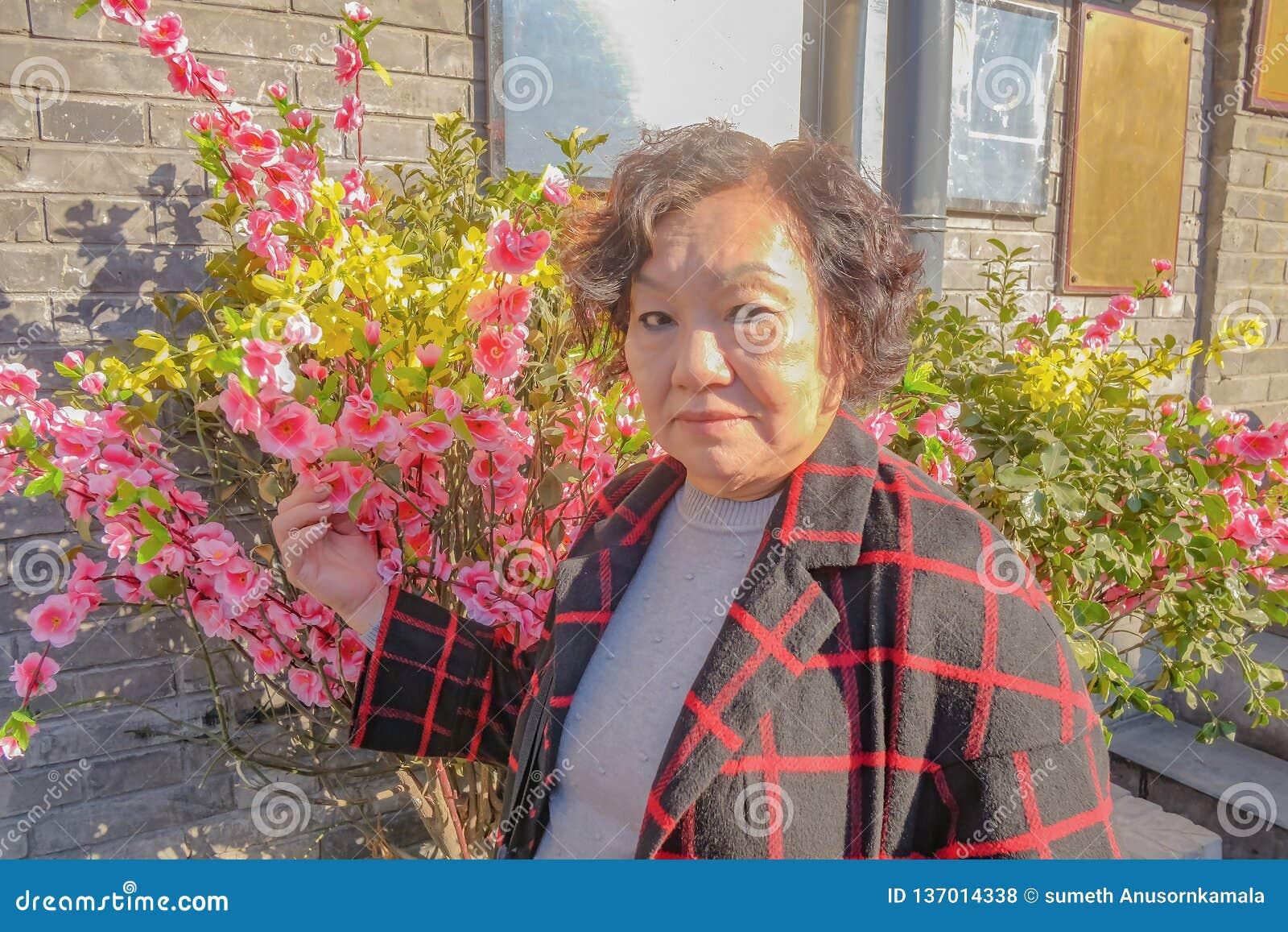 Portret fotografia Azjatyckie starsze podróżnik kobiety z pięknym kwiatem na Nanlouguxiang Stary część teren Pekin