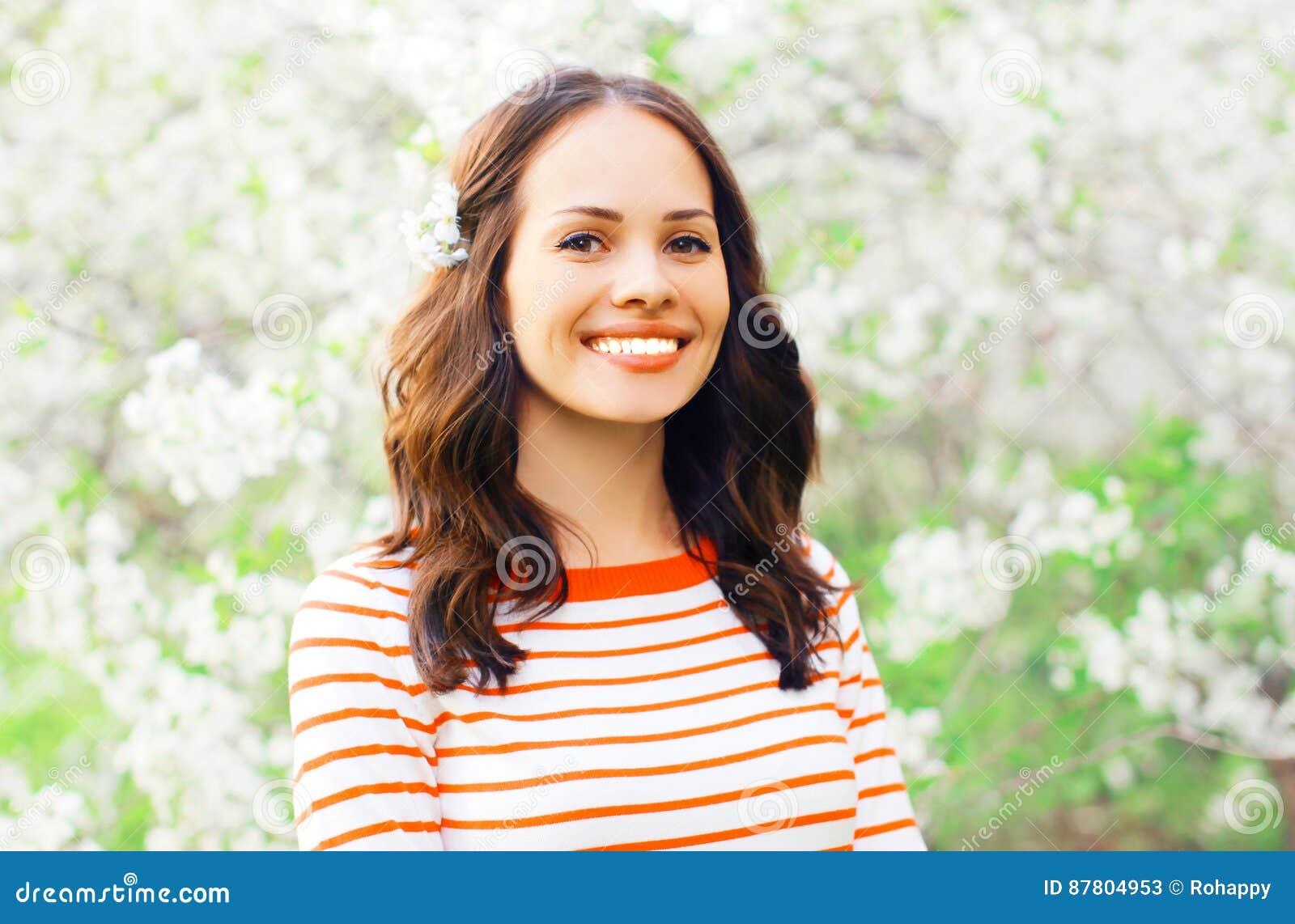 Portret gelukkige glimlachende jonge vrouw over witte de lentebloemen