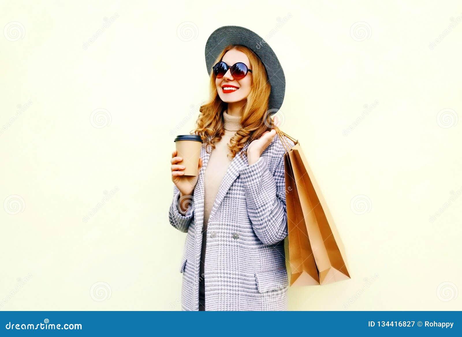 Portret gelukkige glimlachende vrouw die met het winkelen zakken, koffiekop houden, die roze laag, ronde hoed dragen