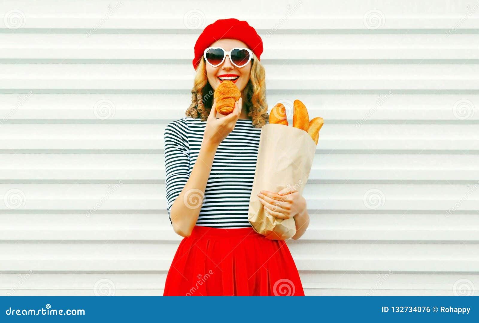 Portret gelukkige vrouw die het document van de croissantholding zak met lon eten