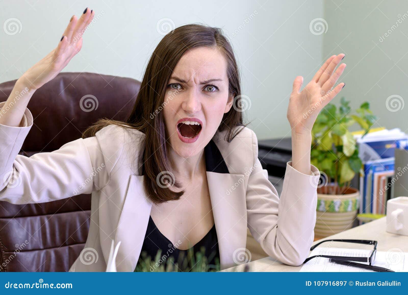 Portret gniewna, krzycząca młoda biznesowa kobieta w rzemiennym krześle za biurowym biurkiem,