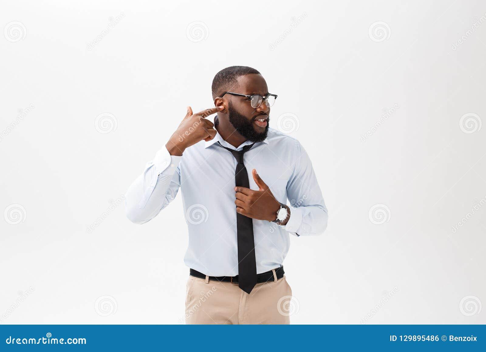 Portret gniewny lub dokuczający młody amerykanin afrykańskiego pochodzenia mężczyzna patrzeje kamerę z nieradym w białej polo kos