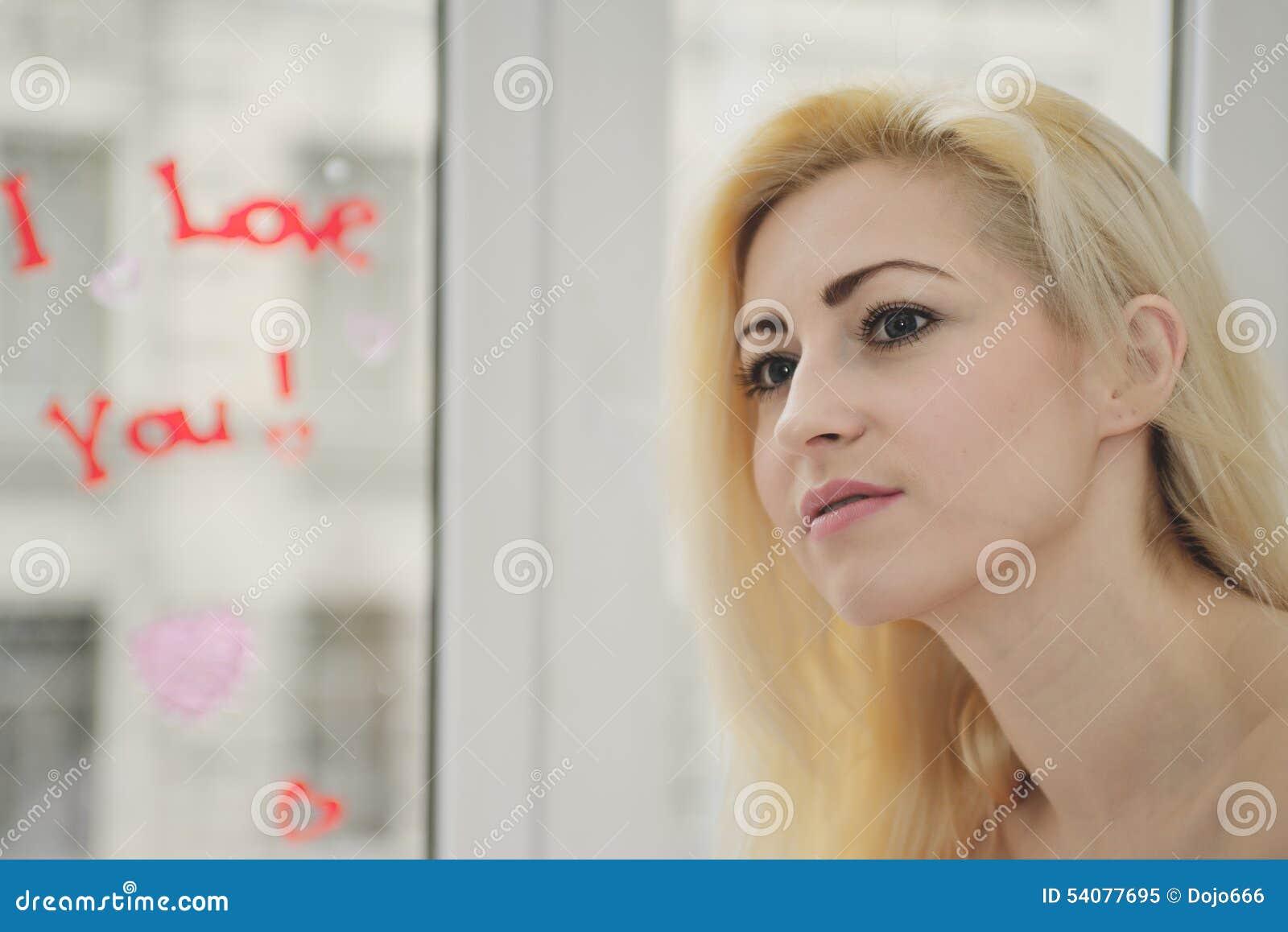 Portret jong meisje met inschrijving bij een venster