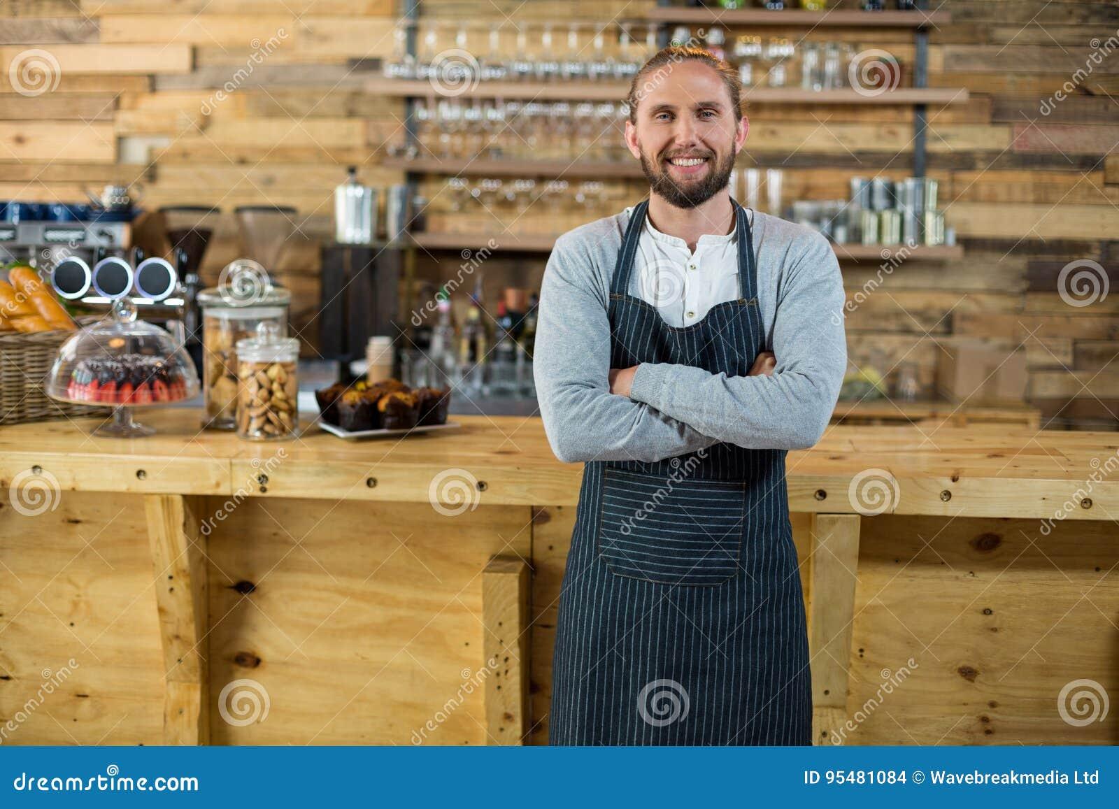 Portret kelner pozycja z rękami krzyżował przy kontuarem