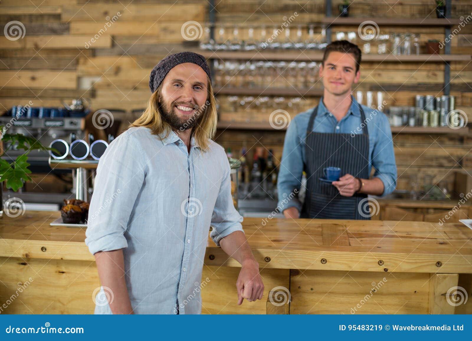 Portret kelner słuzyć filiżanka kawy obsługiwać przy kontuarem