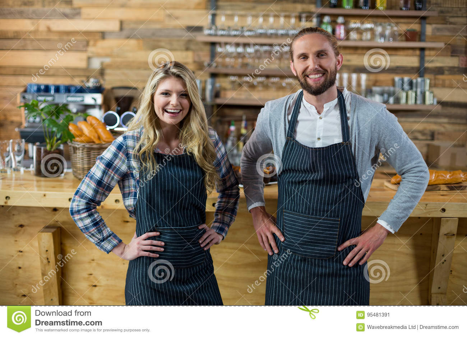 Portret kelnera i kelnerki pozycja z ręką na biodrze przy kontuarem