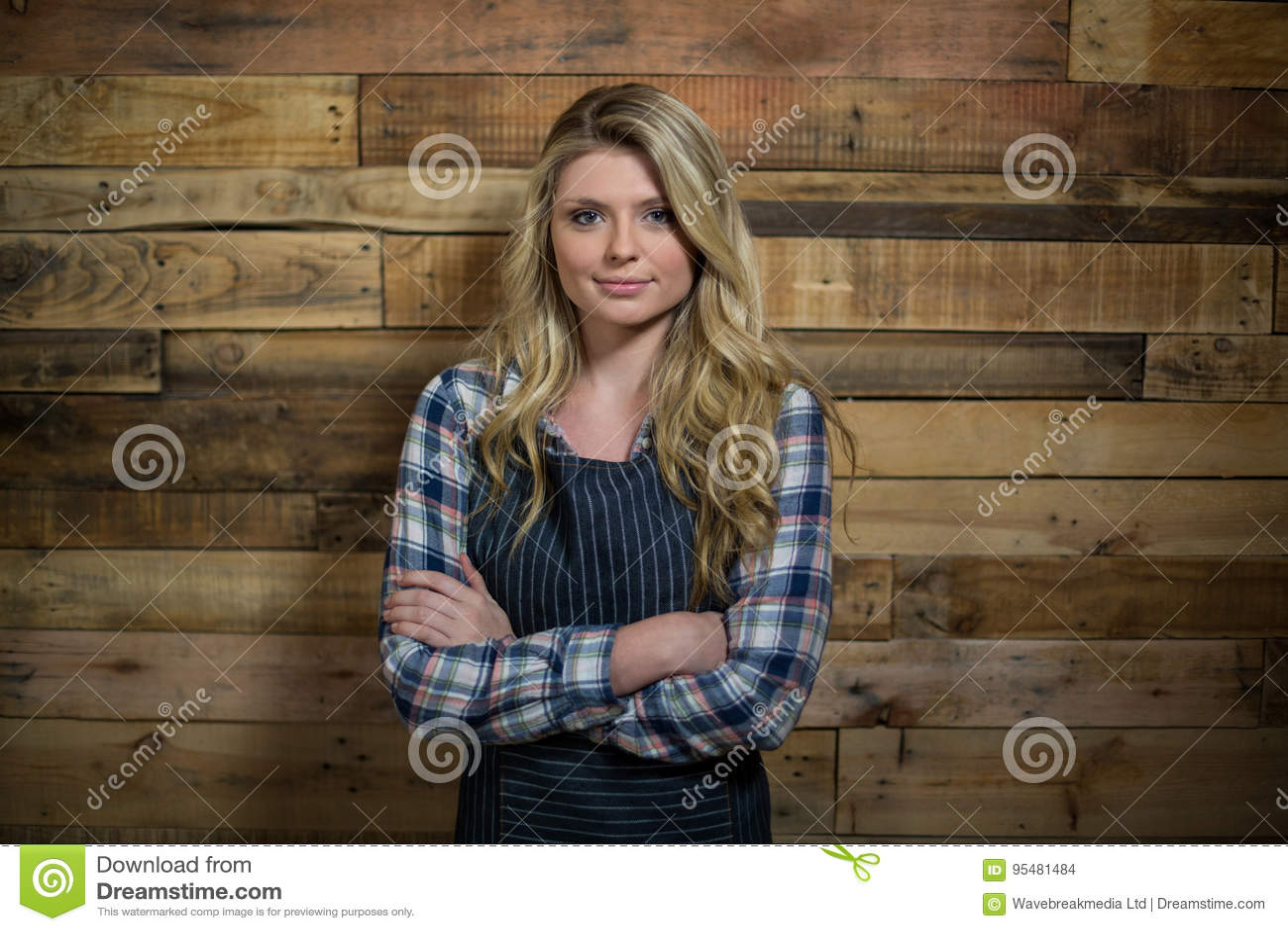 Portret kelnerki pozycja z rękami krzyżował przeciw drewnianej ścianie