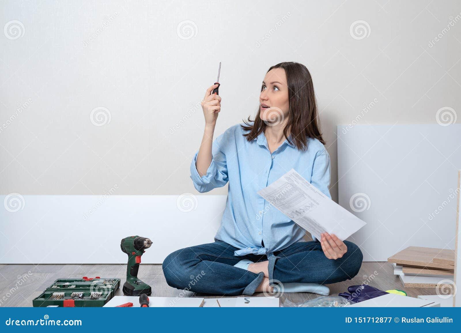 Portret kobieta na podłodze z śrubokrętem i instrukcje dla zgromadzenie meble zdziwiona, intrygująca,