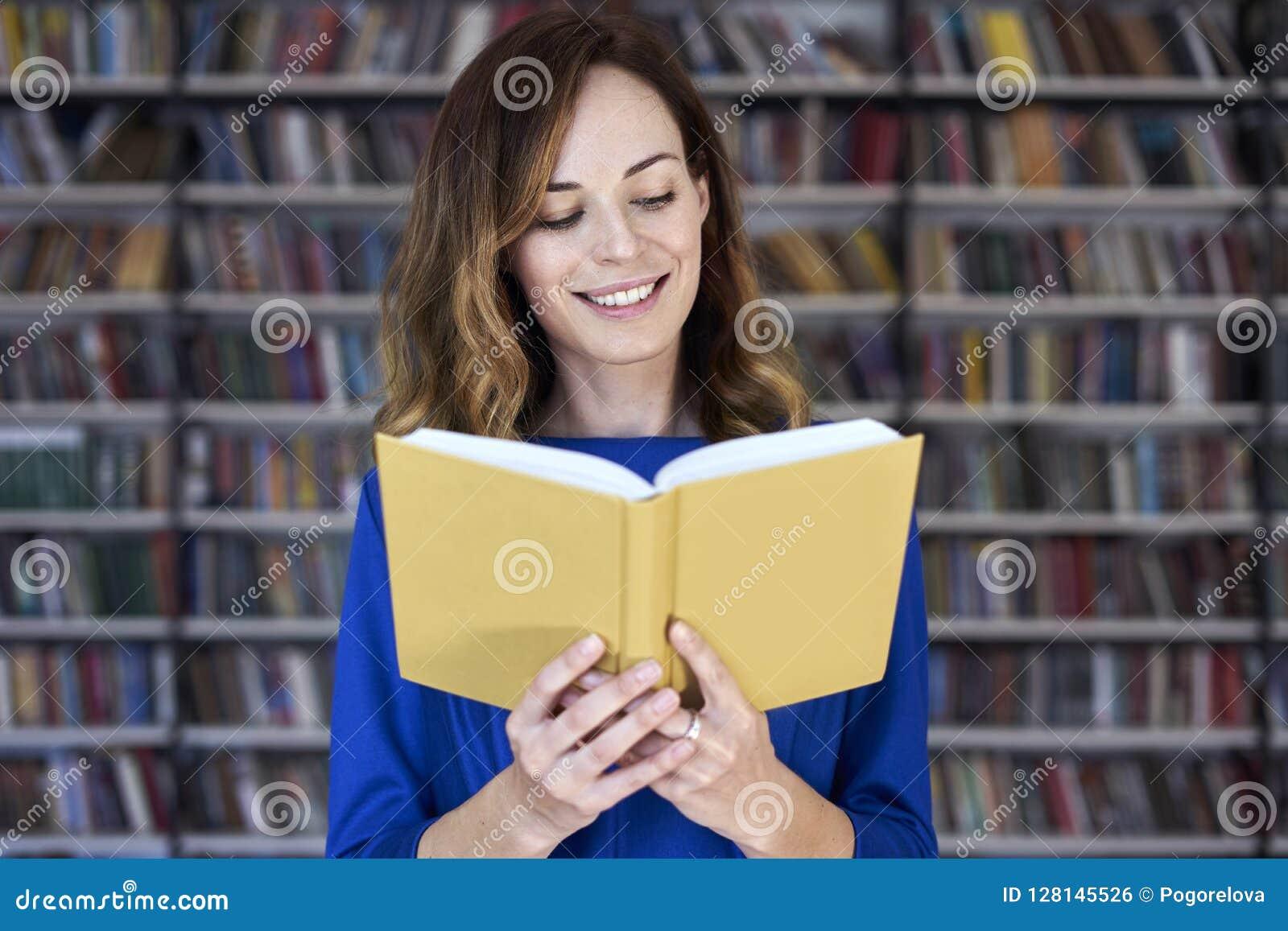 Portret kobieta nad 25 w bibliotecznym czytaniu rozpieczętowana książka, skoncentrowany i mądrze Młody student collegu w działani