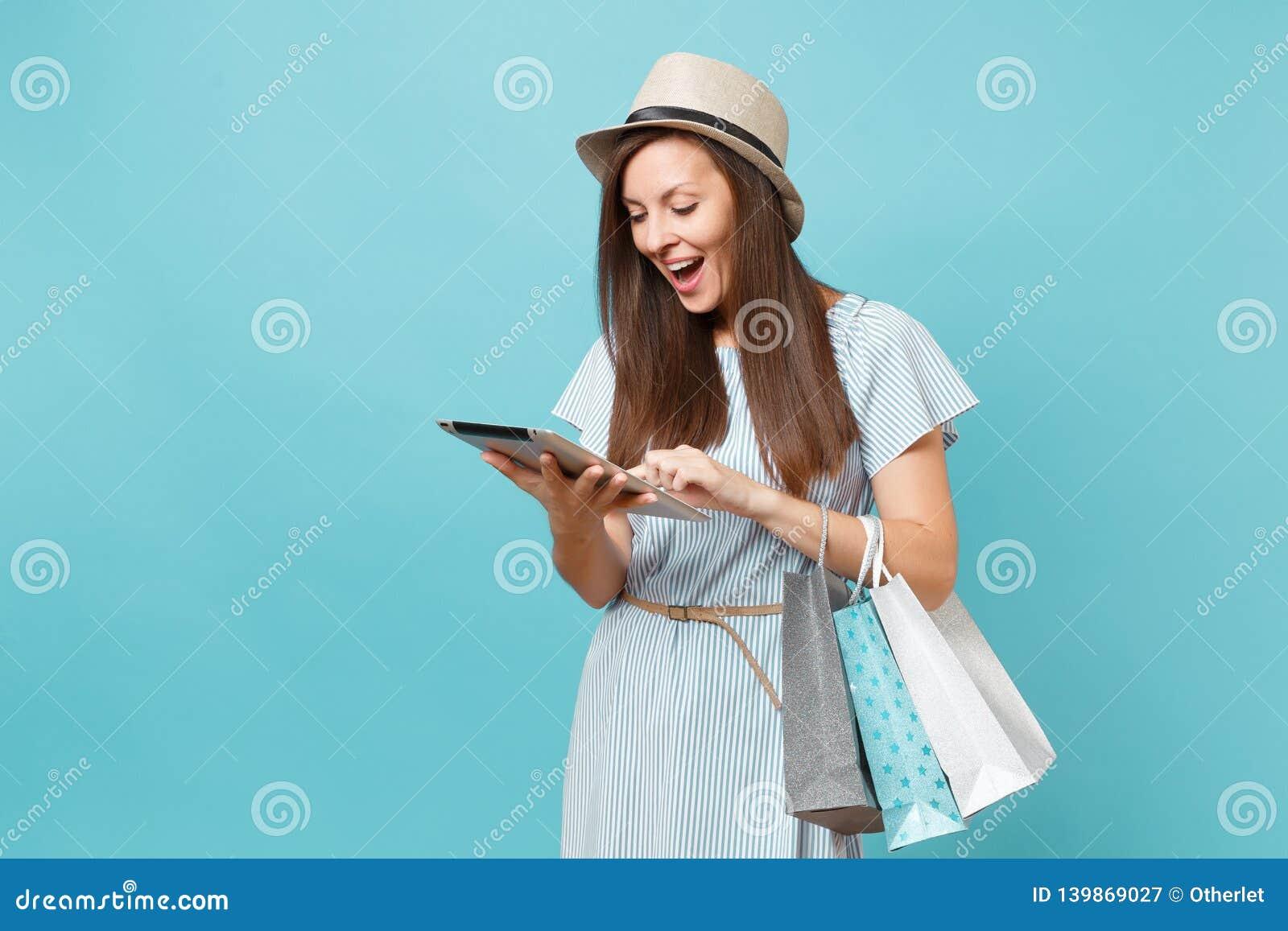 Portret kobieta w lato sukni, słomianego kapeluszu mienie pakuje torby z zakupami po online zakupy, używać pastylka komputer osob