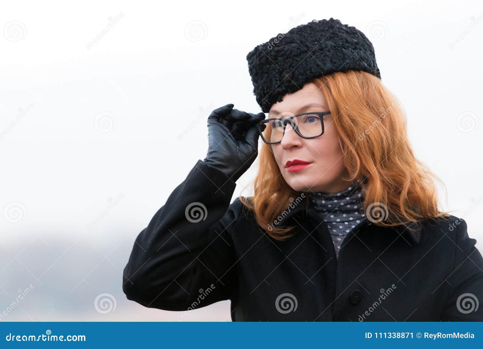 Portret kobieta w szkłach i czarnym żakiecie Skoncentrowana czerwona włosiana kobieta w kapeluszu Portret biznesowa dama z czerwo
