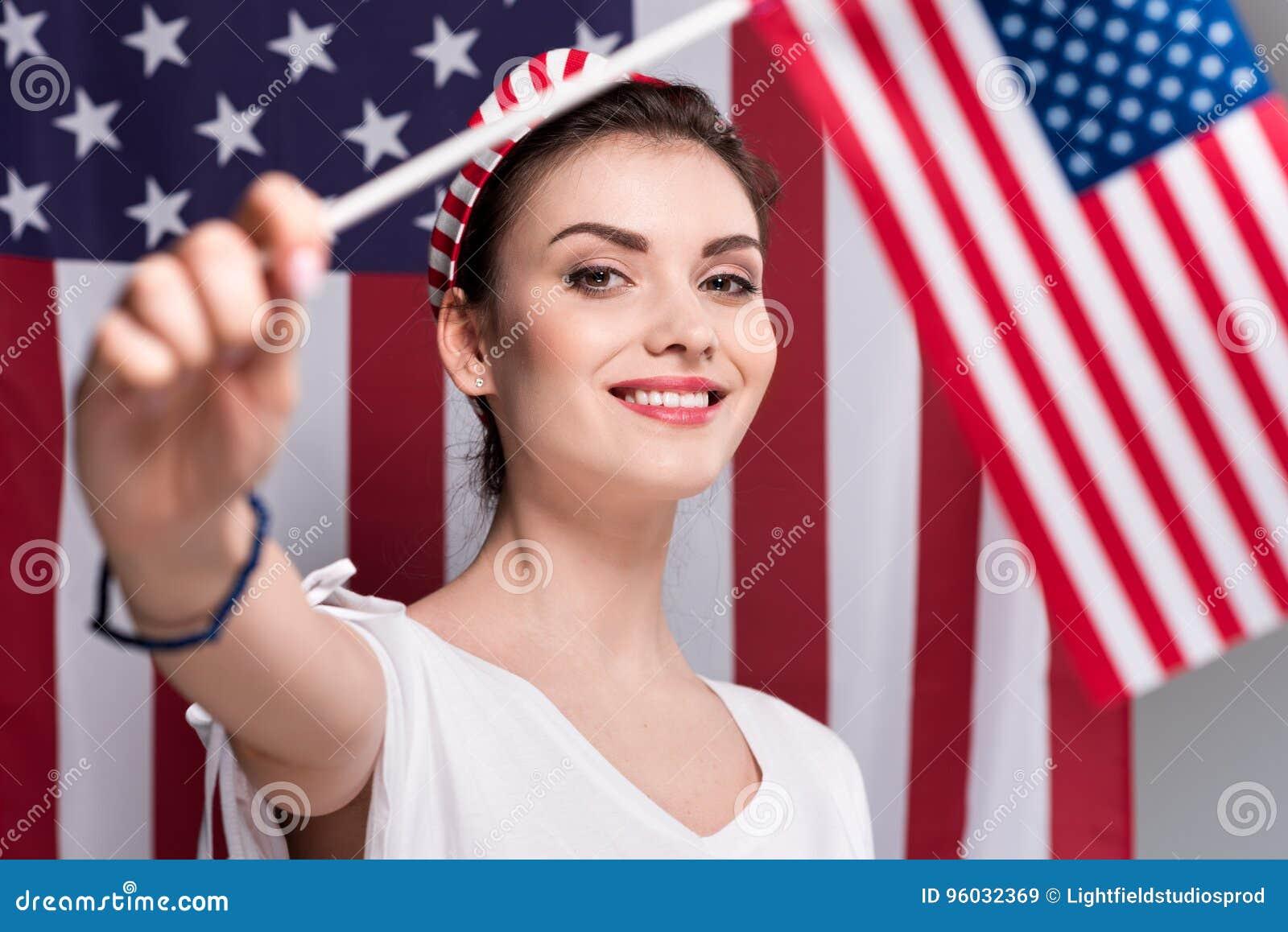 Portret kobiety mienia flaga amerykańska w ręce i patrzeć kamerę