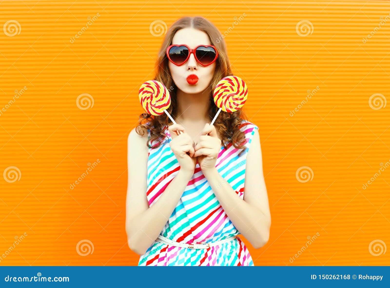 Portret kobiety podmuchowe czerwone wargi trzyma dwa lizaka w serce kształtujących okularach przeciwsłonecznych, kolorowa pasiast