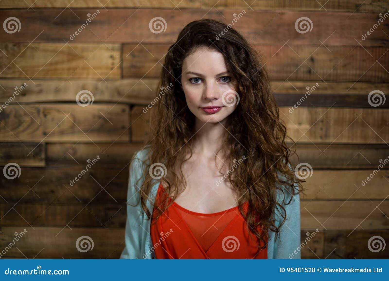 Portret kobiety pozycja przeciw drewnianej ścianie