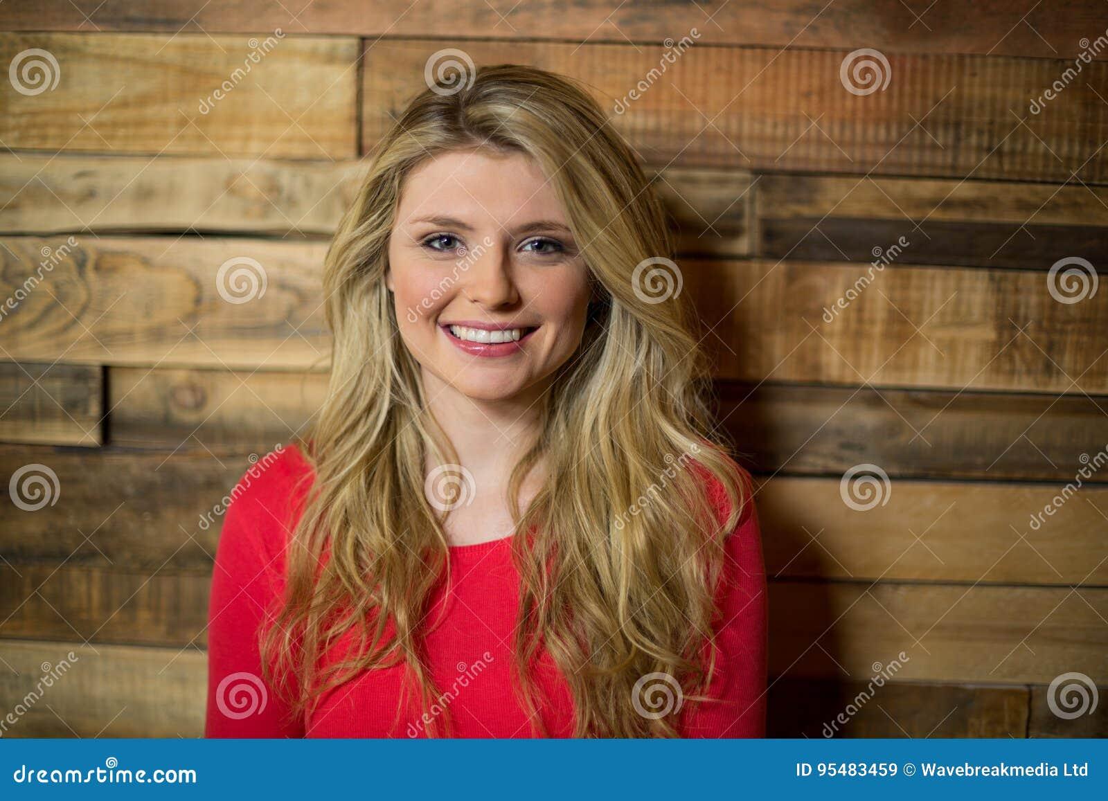 Portret kobiety pozycja przeciw drewnianej ścianie w café