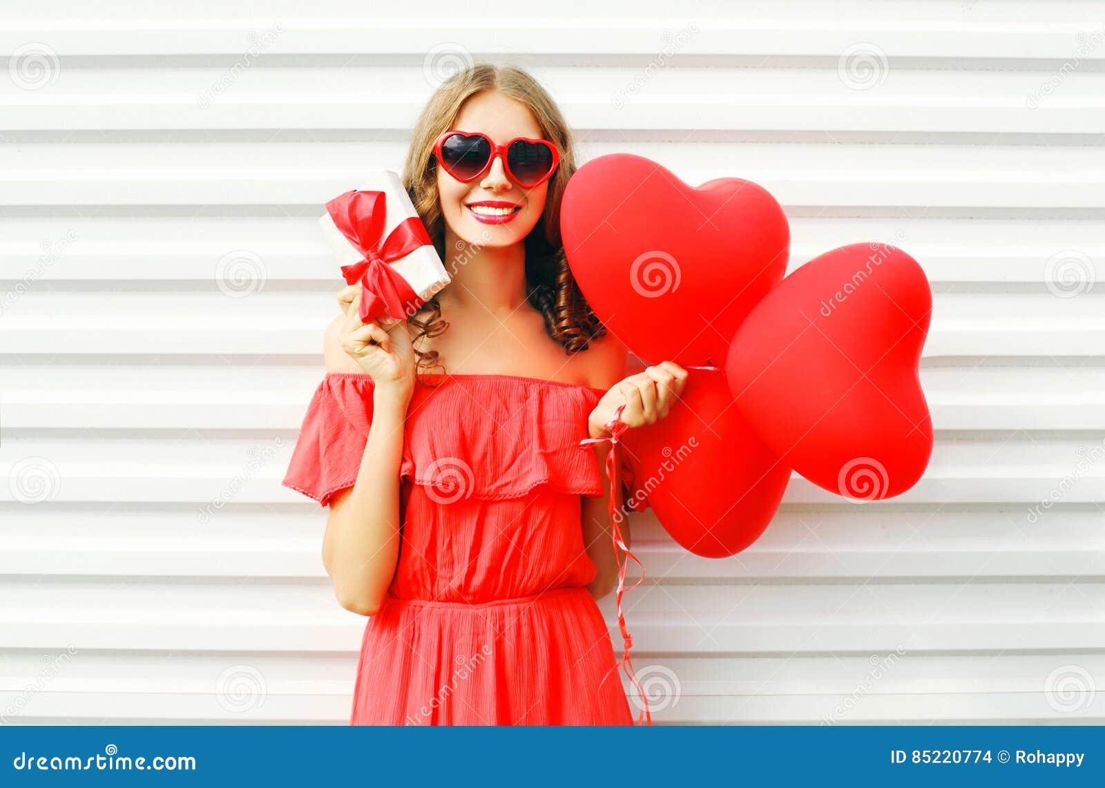 Portret kobiety szczęśliwy uśmiechnięty mienie w ręka prezenta pudełku i czerwony lotniczych balonów kierowy kształt nad bielem