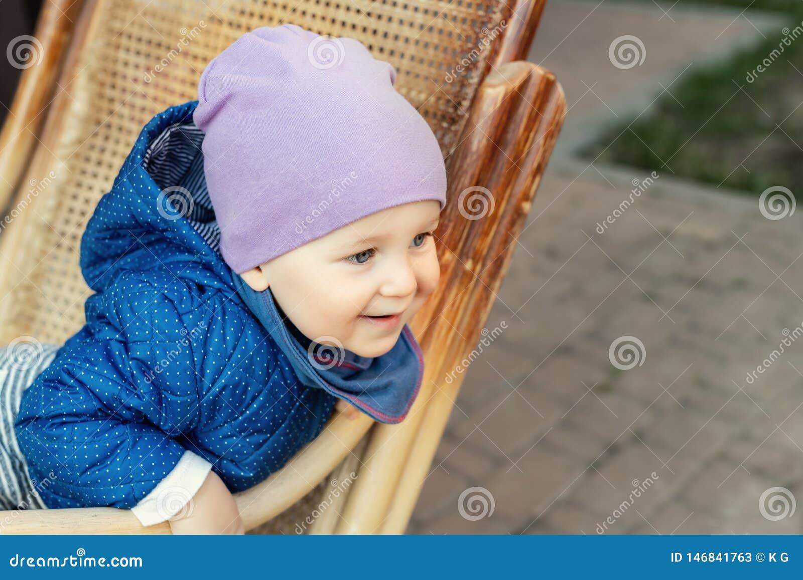 Portret ?liczna urocza caucasian ch?opiec ma zabawy obsiadanie w drewnianym rattan ko?ysa krzes?a na domu tarasu podw?rko outdoor