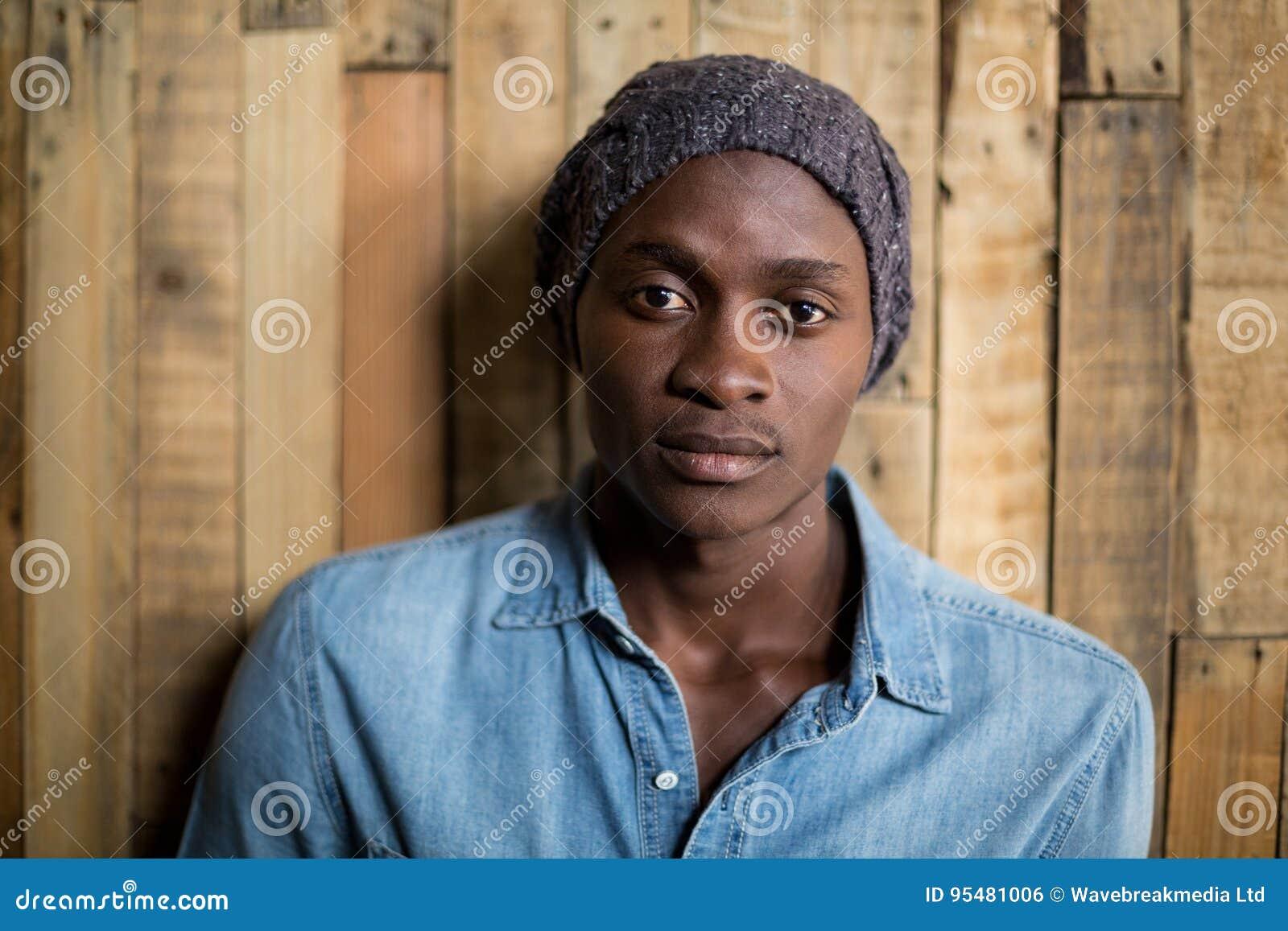 Portret mężczyzna pozycja przeciw drewnianej ścianie