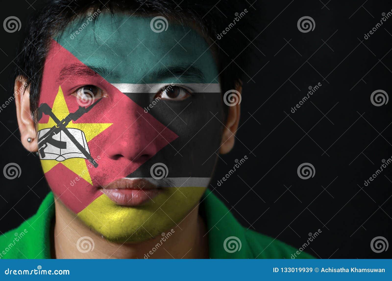 Portret mężczyzna z flagą Mozambik malował na jego twarzy na czarnym tle