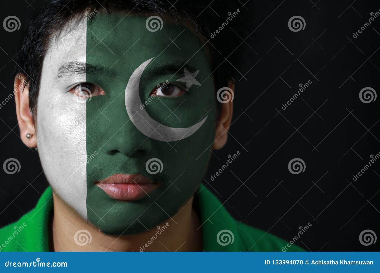 Portret mężczyzna z flagą Pakistan malował na jego twarzy na czarnym tle