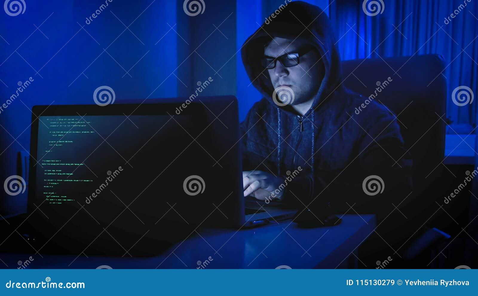 Portret męski hacker w hoodie obsiadaniu w ciemnym pokoju i działaniu na komputerze