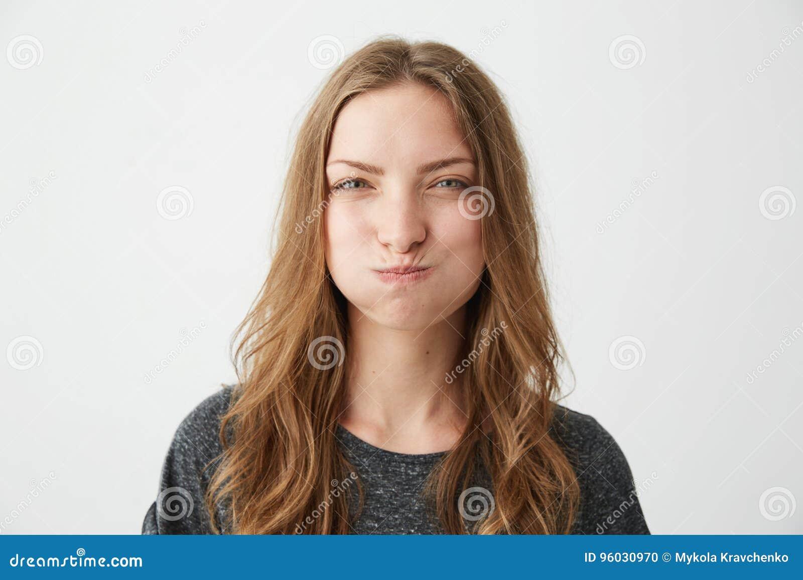 Portret młoda ładna obrażająca dziewczyna patrzeje kamerę marszczy brwi nad białym tłem z śmieszną twarzą