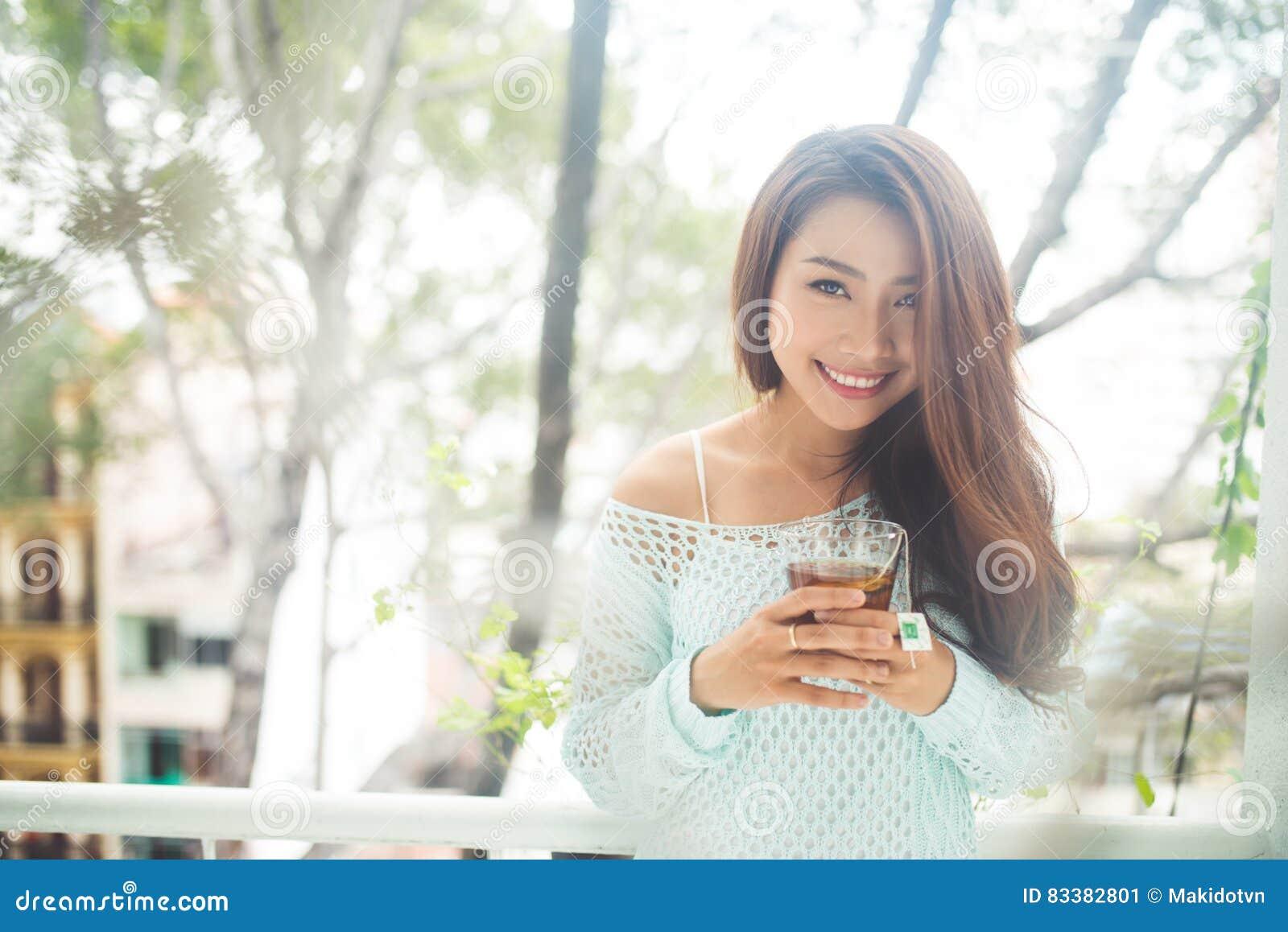Portret młoda azjatykcia kobieta pije jej ranek herbaty Spadał r