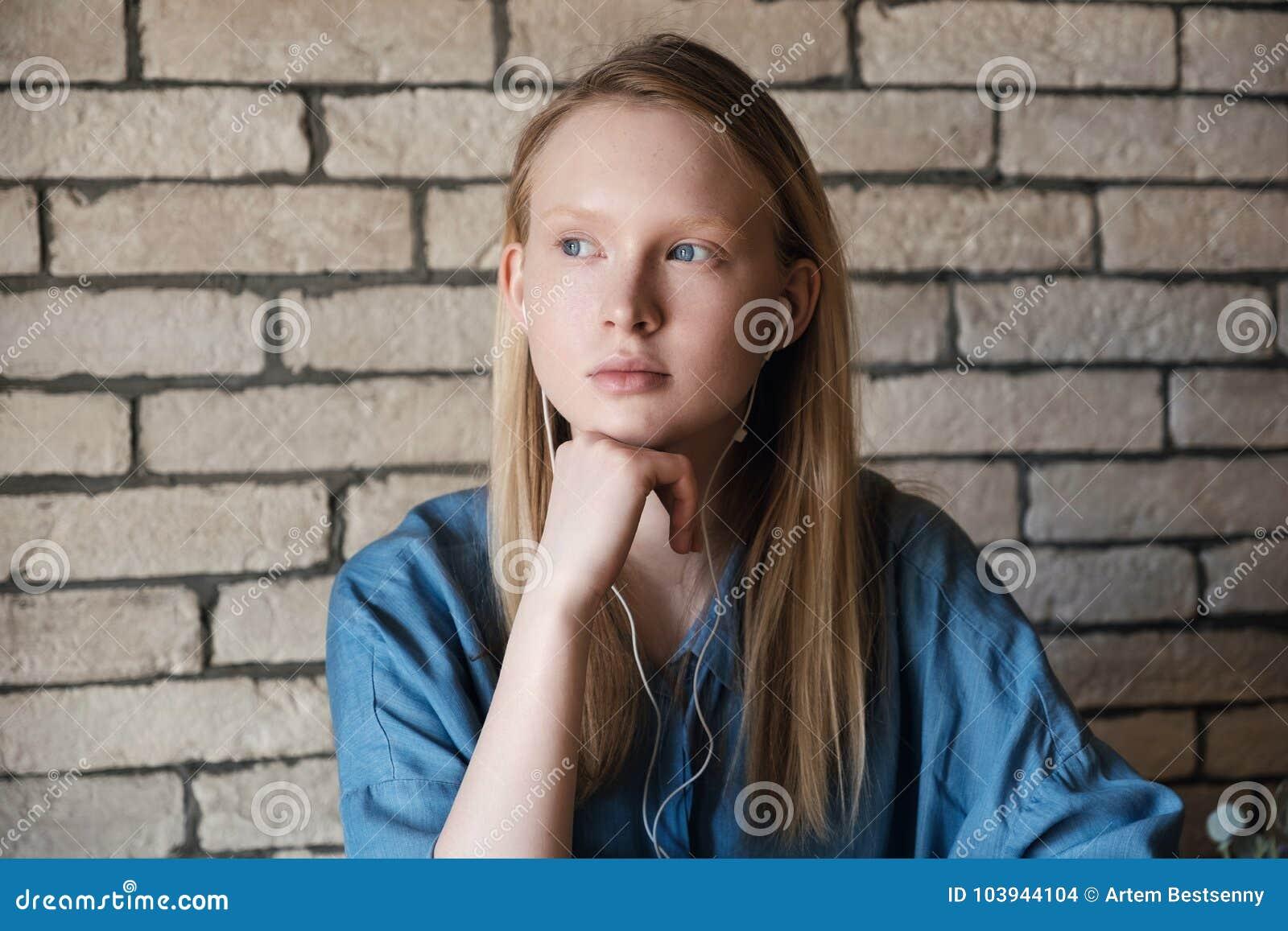 Portret młoda blondynki dziewczyna z hełmofonami Dziewczyny głowa odpoczywa na jej ręce