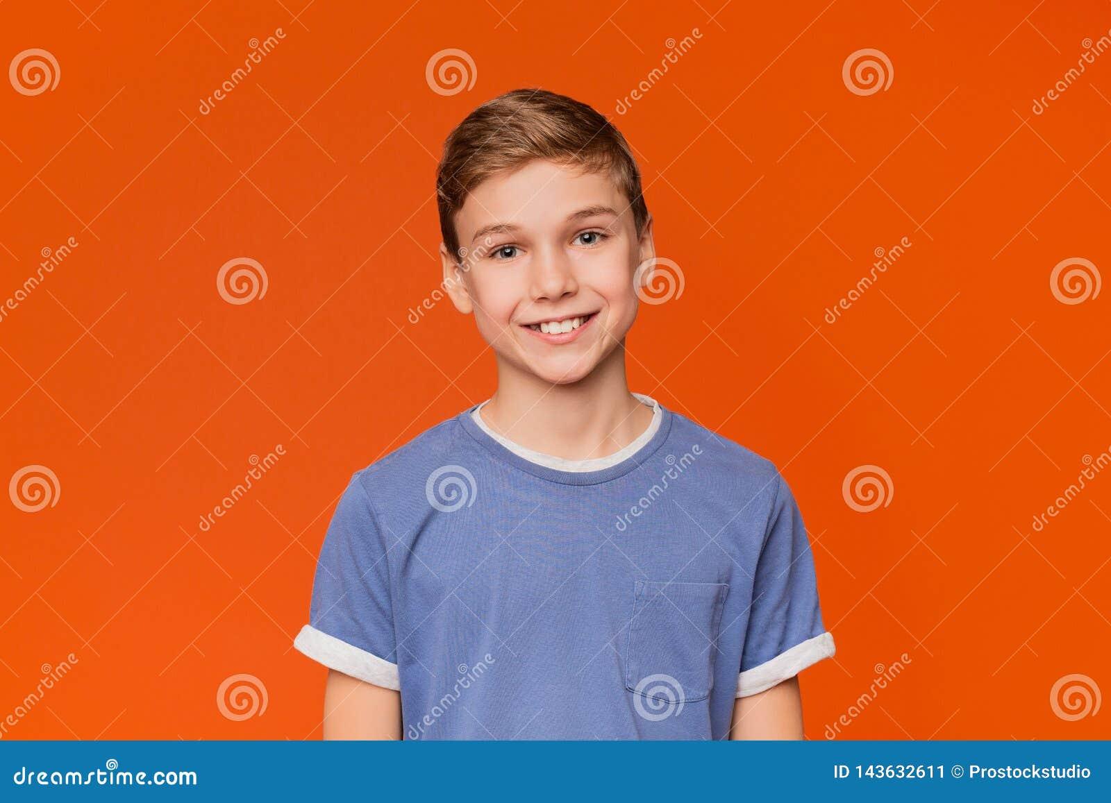 Portret młoda chłopiec na pomarańczowym tle