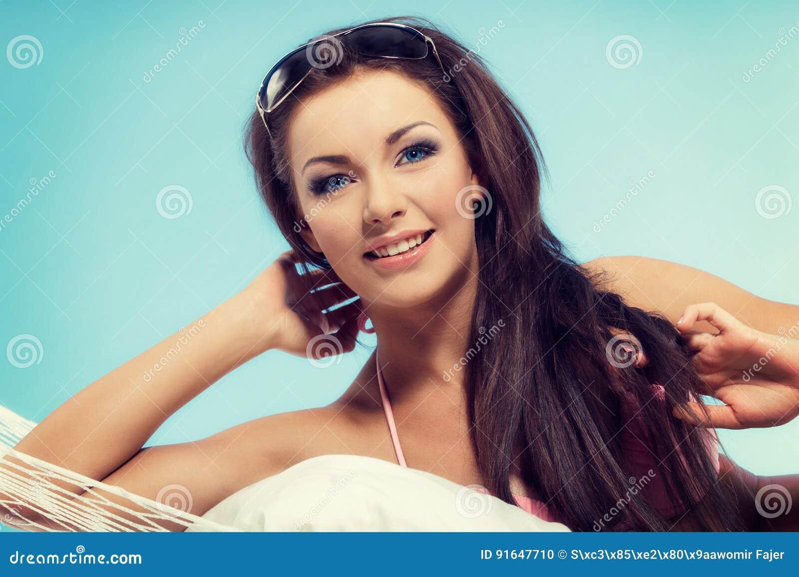 Portret młoda kobieta relaksuje w hamaku w urlopowym czasie w bikini