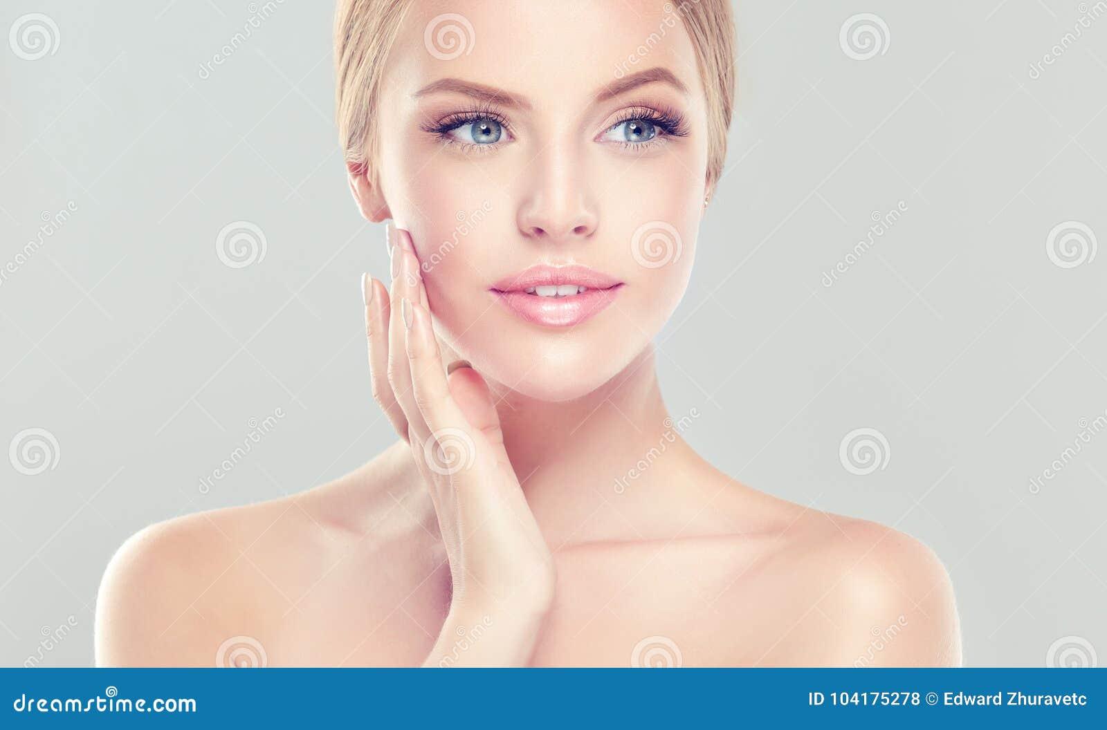 Portret młoda kobieta z czystą świeżą skórą i miękką częścią, delikatny uzupełniał Kobieta dotyka tenderly swój twarz
