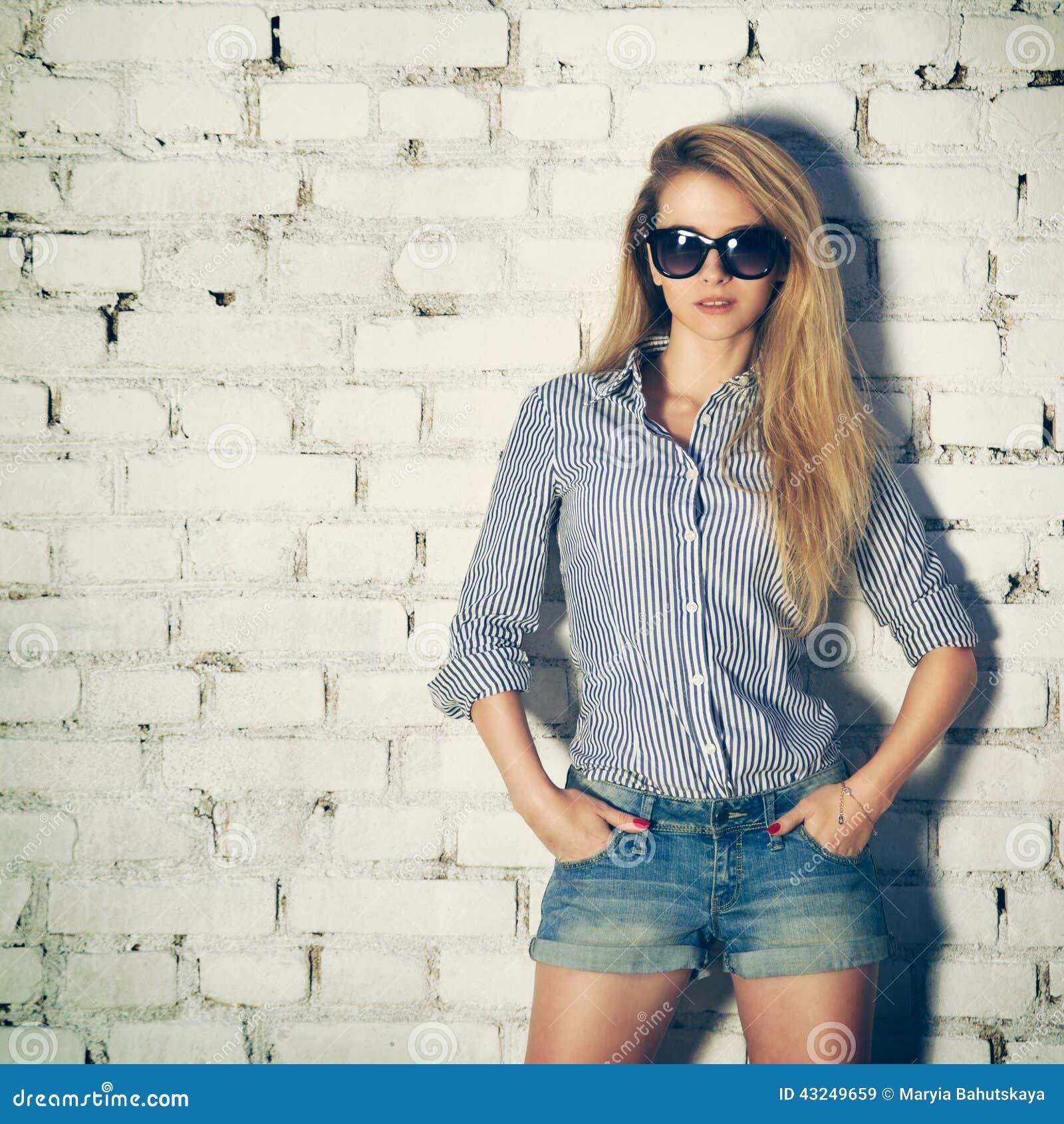 Portret Młoda modniś kobieta przy ściana z cegieł