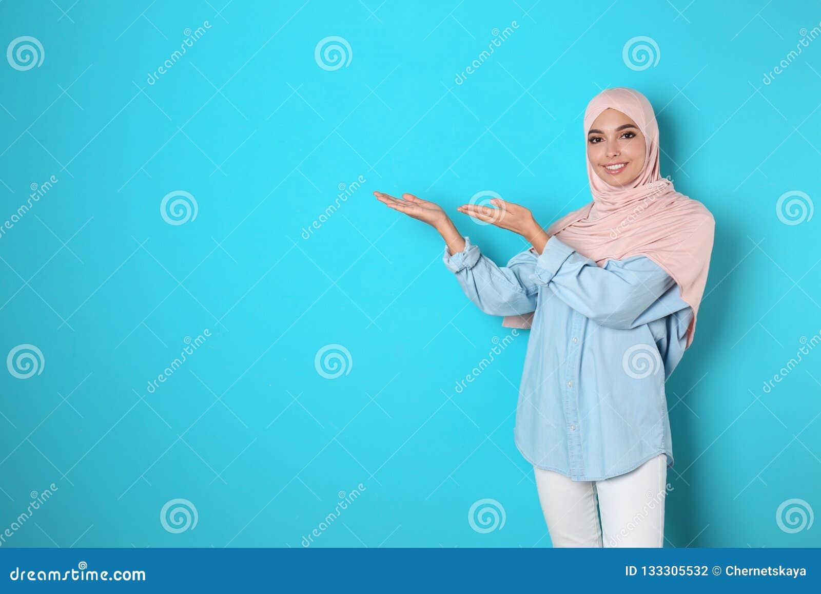 Portret młoda Muzułmańska kobieta w hijab przeciw koloru tłu