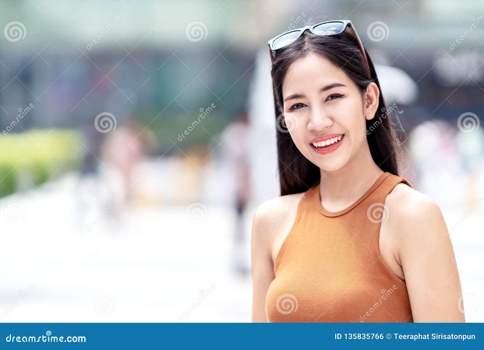 Portret młoda piękna azjatykcia kobieta, blogger, vlogger lub elegancka moda uśmiechnięta i patrzeje kamerę, jest ubranym z ramie