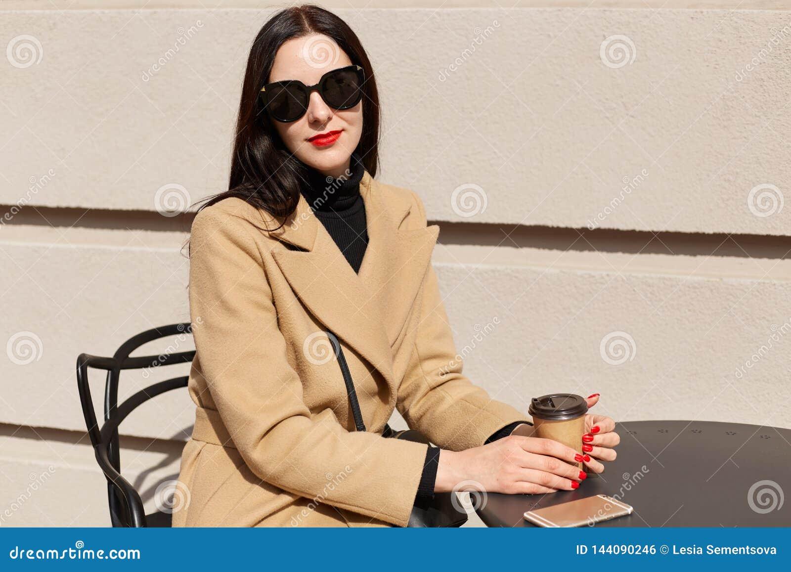 Portret młoda piękna brunetki kobieta w eleganckich okularach przeciwsłonecznych i beżowym modnym żakiecie siedzi przy stołem w p