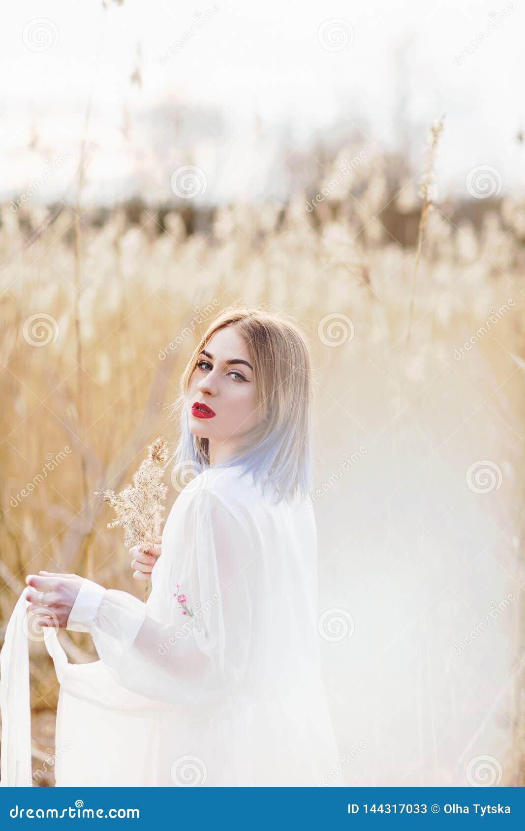 Portret młoda piękna dziewczyna w białej sukni w pszenicznym polu, odprowadzenie, beztroski Cieszyć się pięknego słonecznego dzie