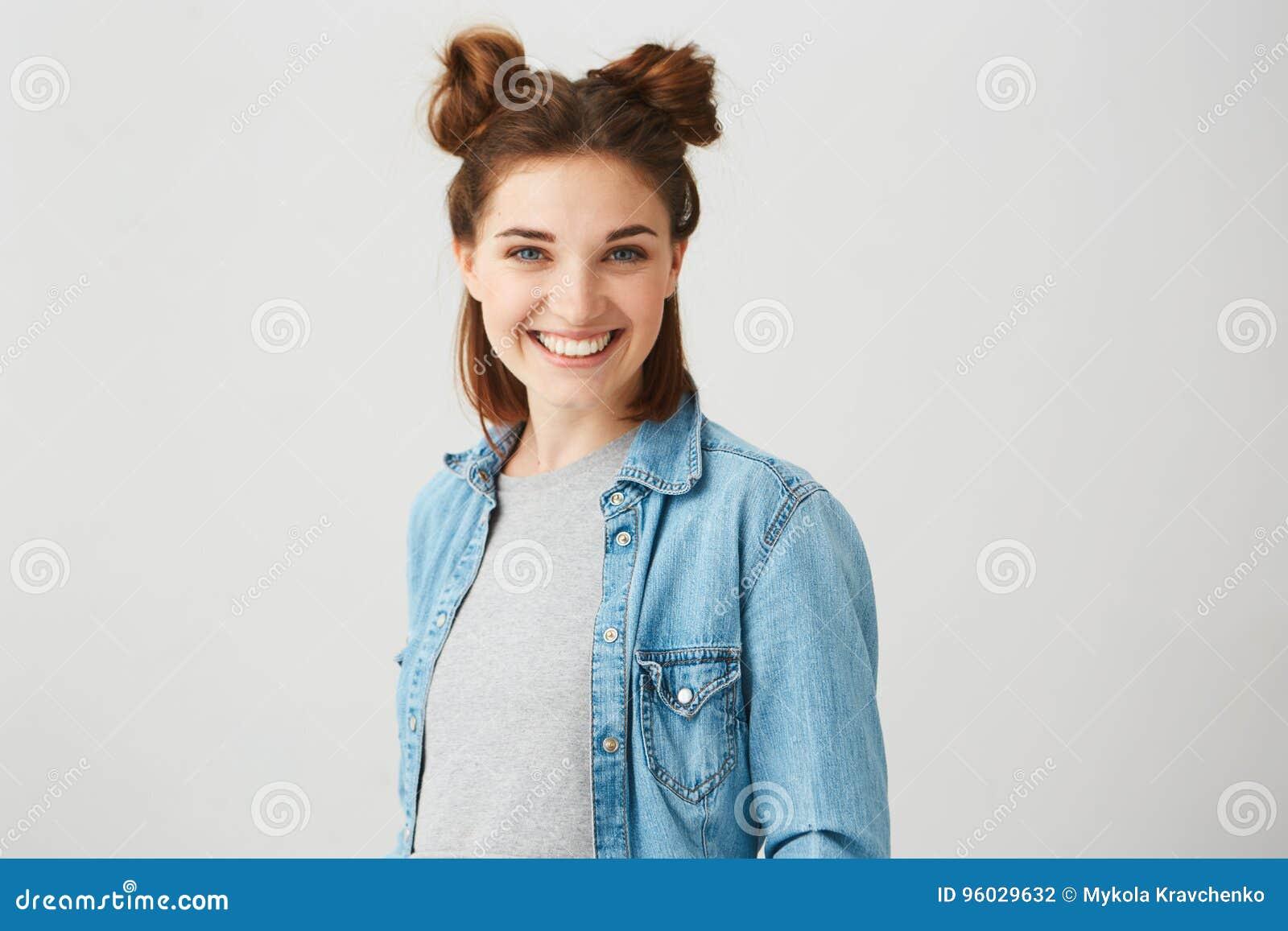 Portret młoda piękna nastoletnia dziewczyna ono uśmiecha się z dwa babeczkami patrzejący kamerę nad białym tłem