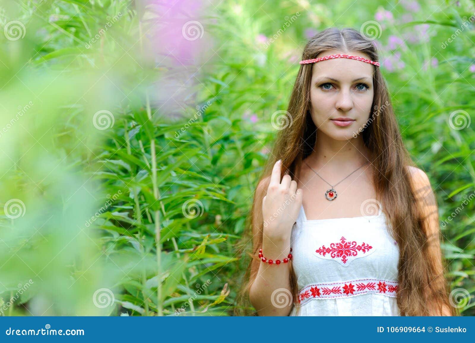 Portret młoda piękna Slawistyczna dziewczyna z długie włosy i Slawistyczną etniczną suknią w gąszczach wysoka trawa