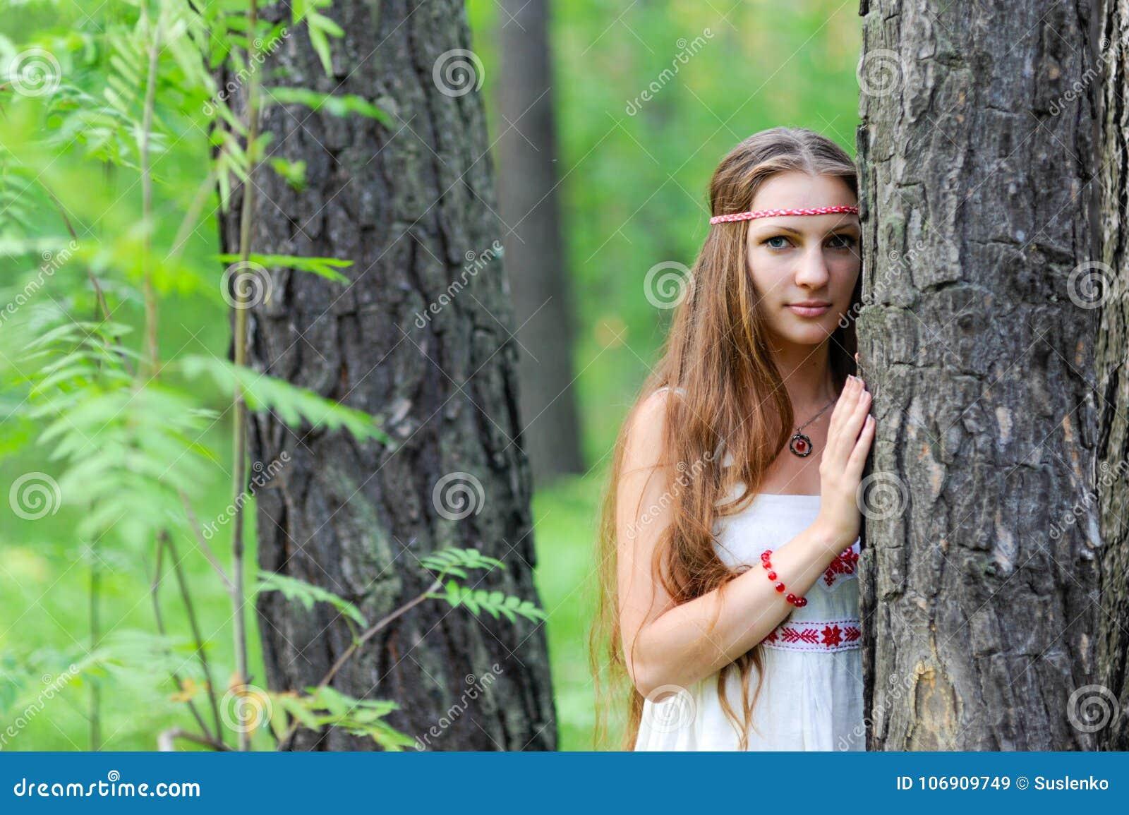 Portret młoda piękna Slawistyczna dziewczyna z długie włosy i Slawistyczną etniczną suknią w lato lesie