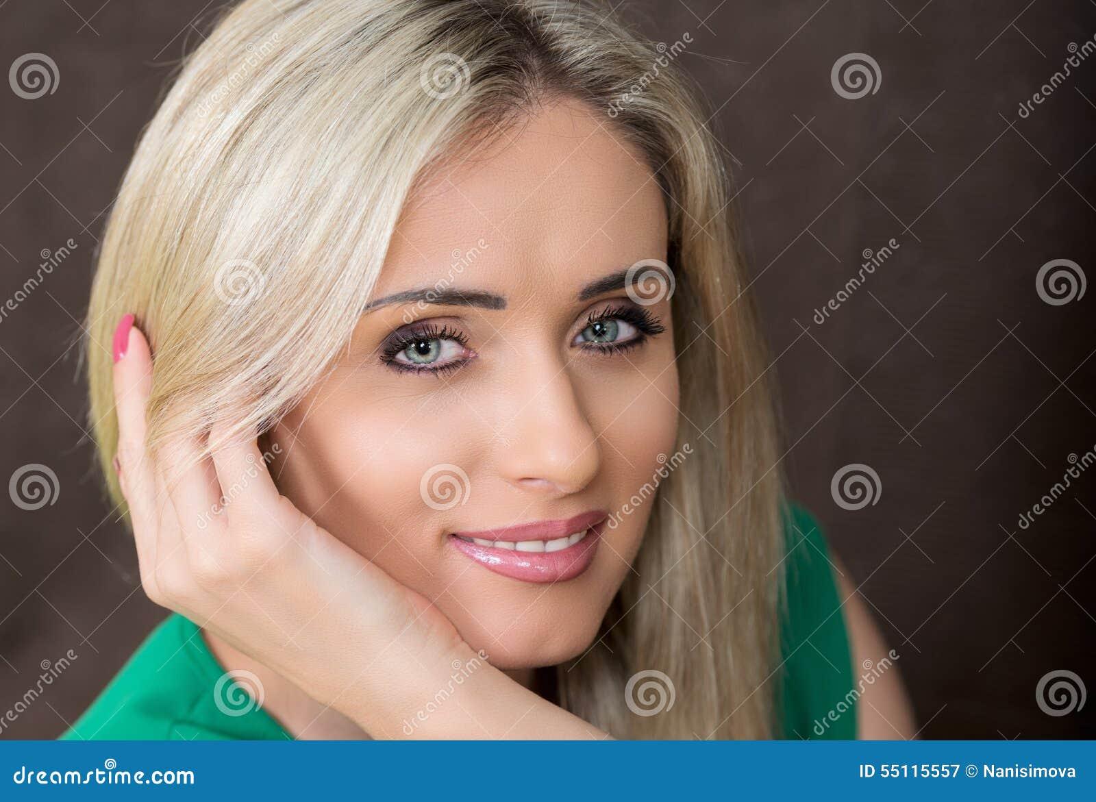 Portret młoda uśmiechnięta blond kobieta w zieleni sukni