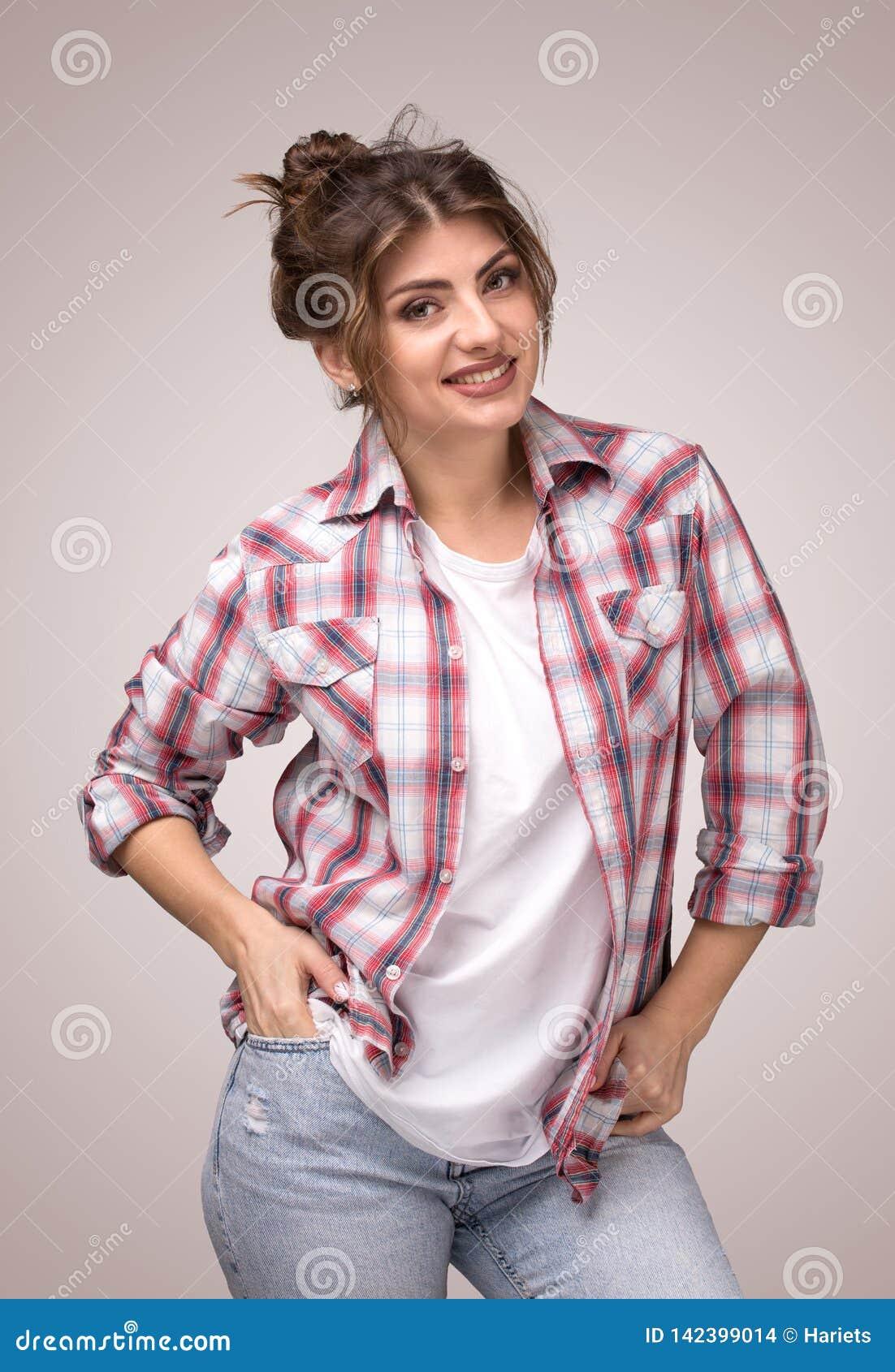 Portret młoda uśmiechnięta kobieta w szkockiej kraty koszula i białej koszulce, stoi z rękami w kieszeniach