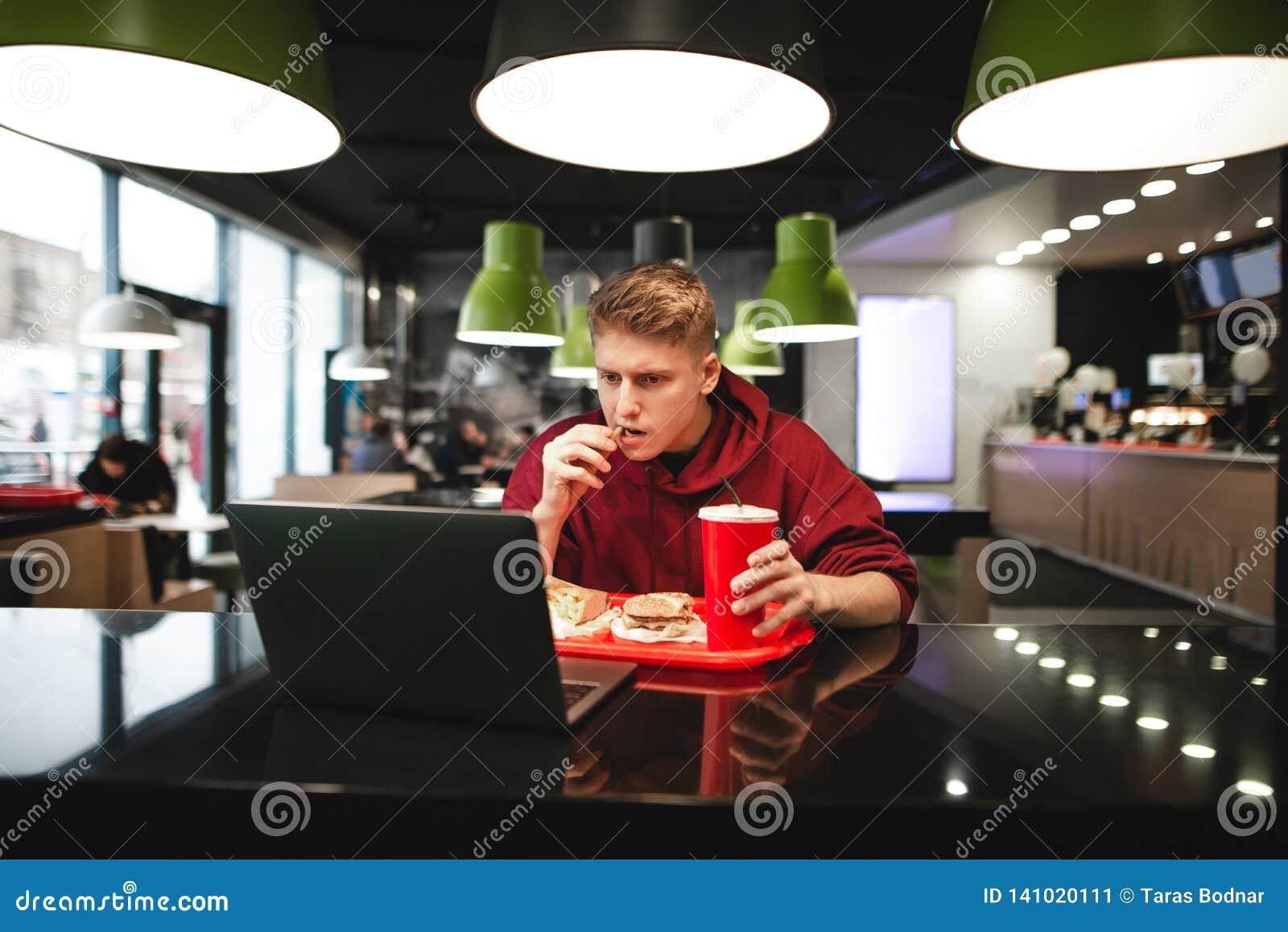 Portret młodego człowieka łasowania fast food przy restauracją i używać laptop
