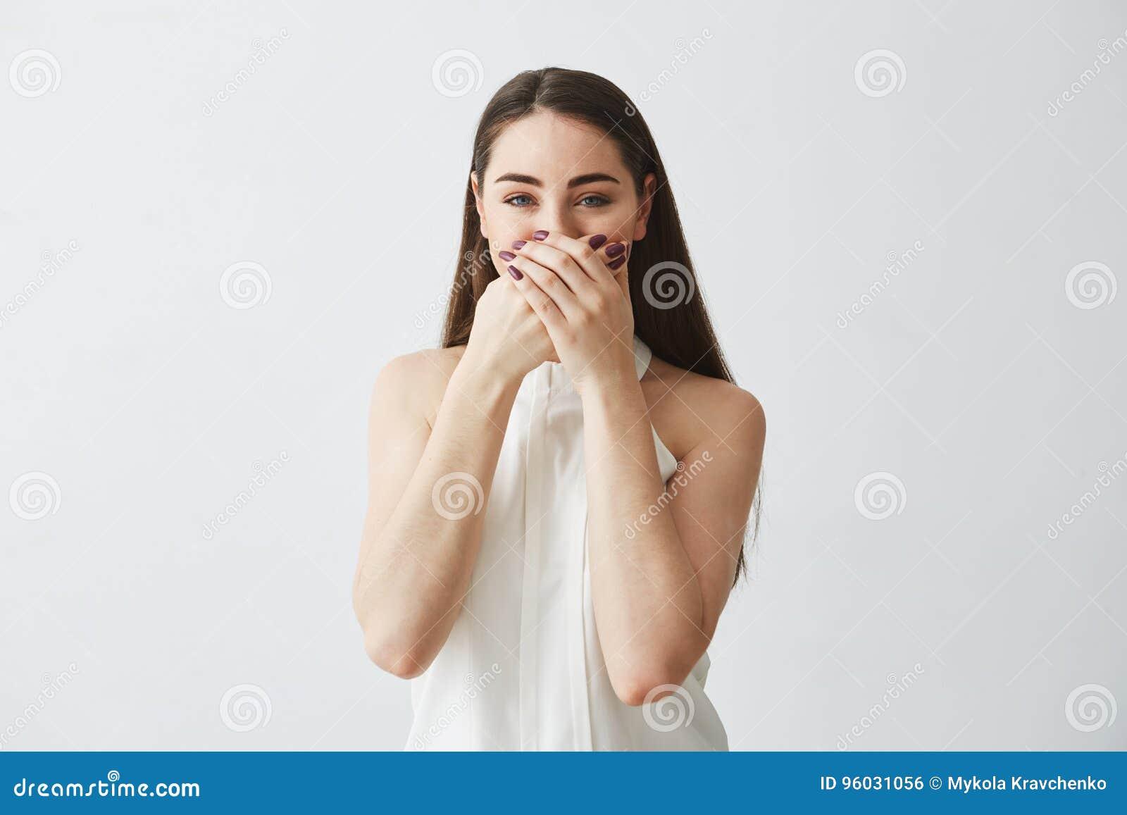Portret młodej brunetki dziewczyny roześmiany nakrywkowy usta z ręką patrzeje kamerę nad białym tłem