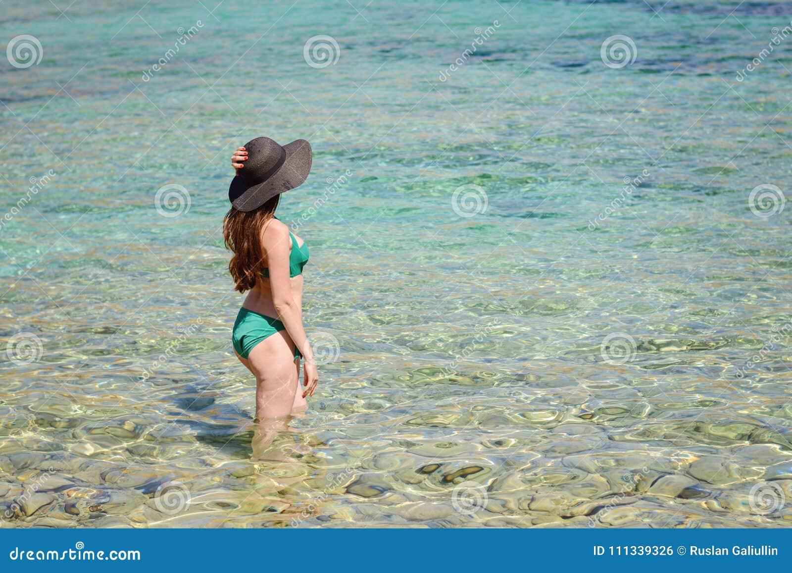 Portret młodej kobiety brunetka jest ubranym czarnego kapelusz, zieleni swimsuit pozycja w szmaragdowej wodzie morskiej, copyspac