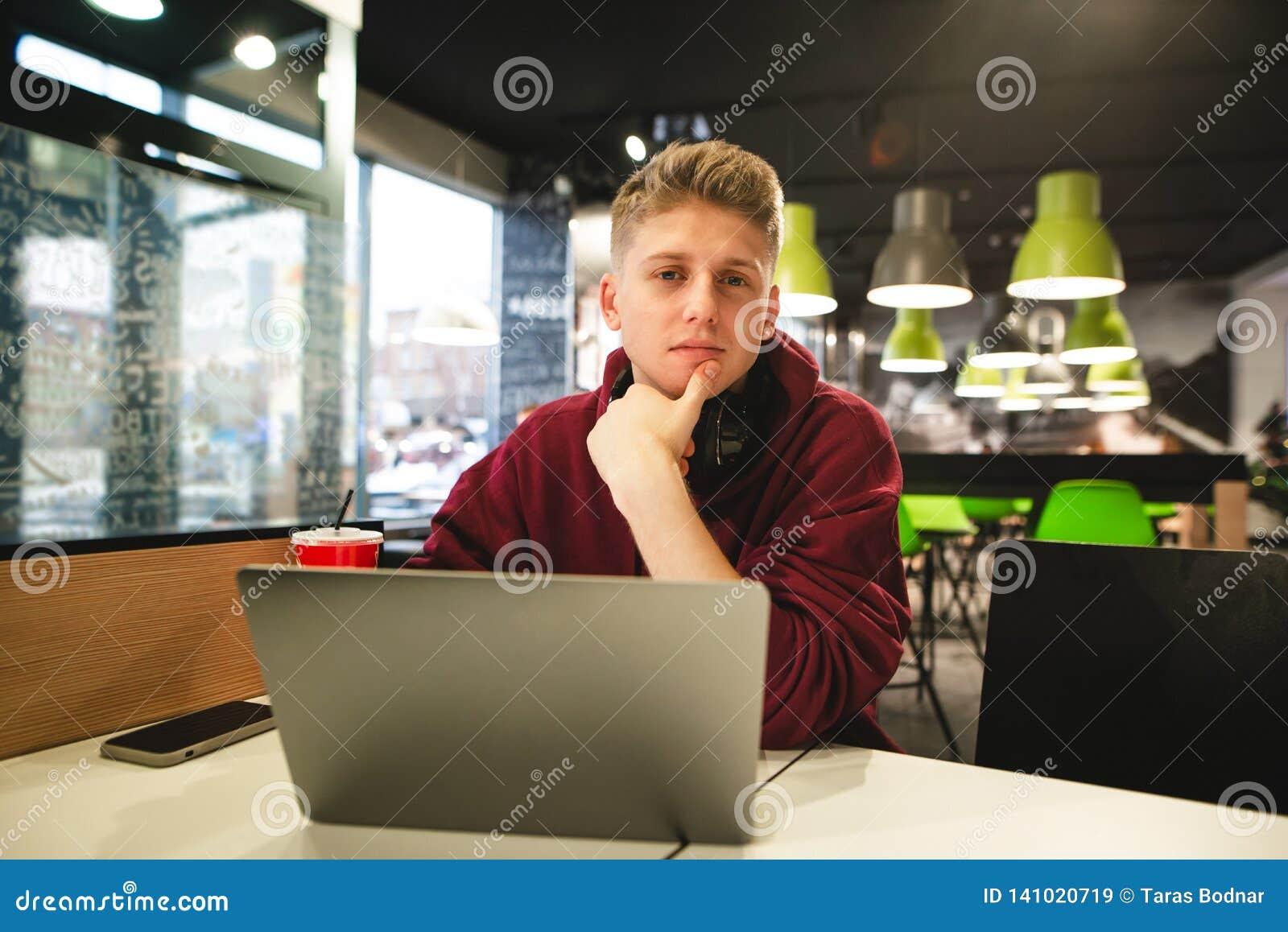 Portret młody człowiek w przypadkowej odzieży obsiadaniu z laptopem w fast food kawiarni, patrzeje kamerę