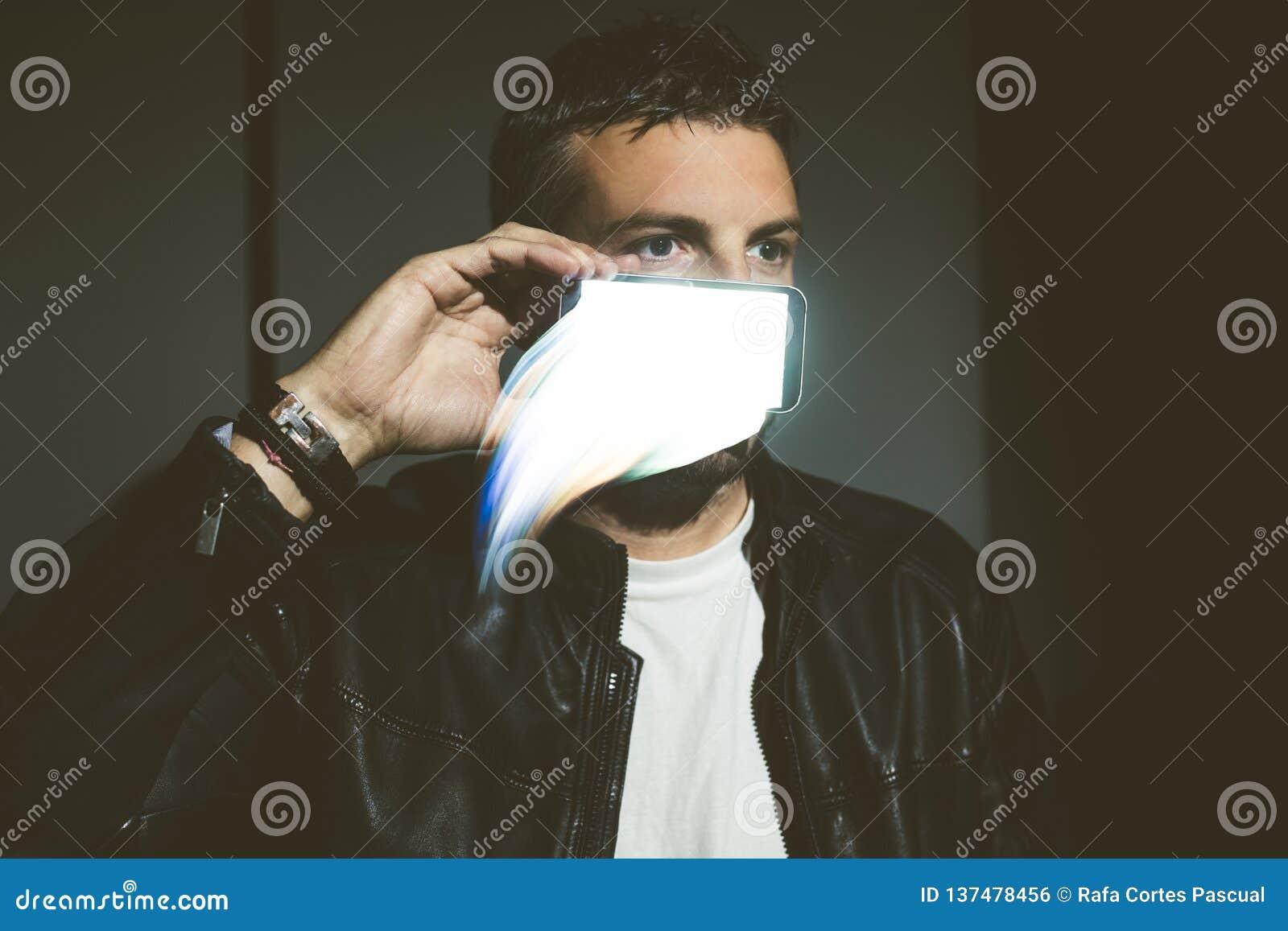 Portret młody człowiek z futurystycznym telefonem komórkowym Abstrakcjonistyczny pojęcie technologia
